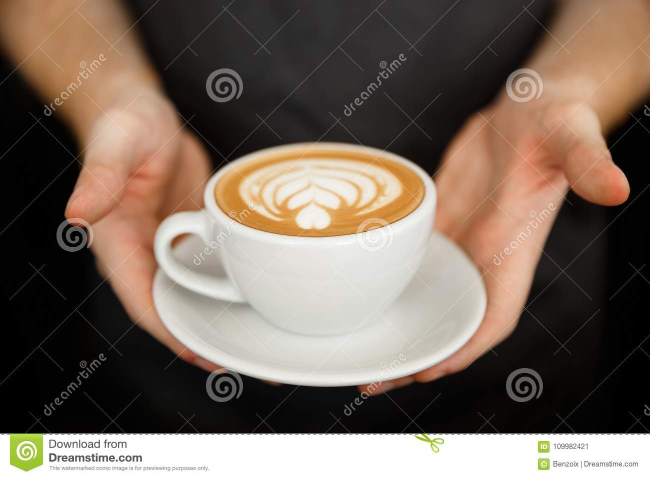 Coffee Business Concept - Cropped Close up of female serving coffee with latte art while standing in coffee shop. Focus