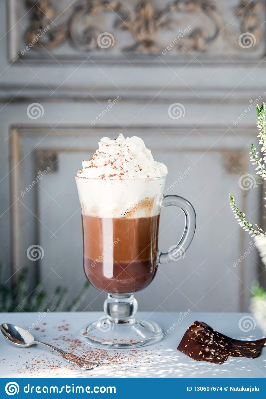 Coffee with chocolate and whipped cream in a transparent glass against the background of a vintage wall.