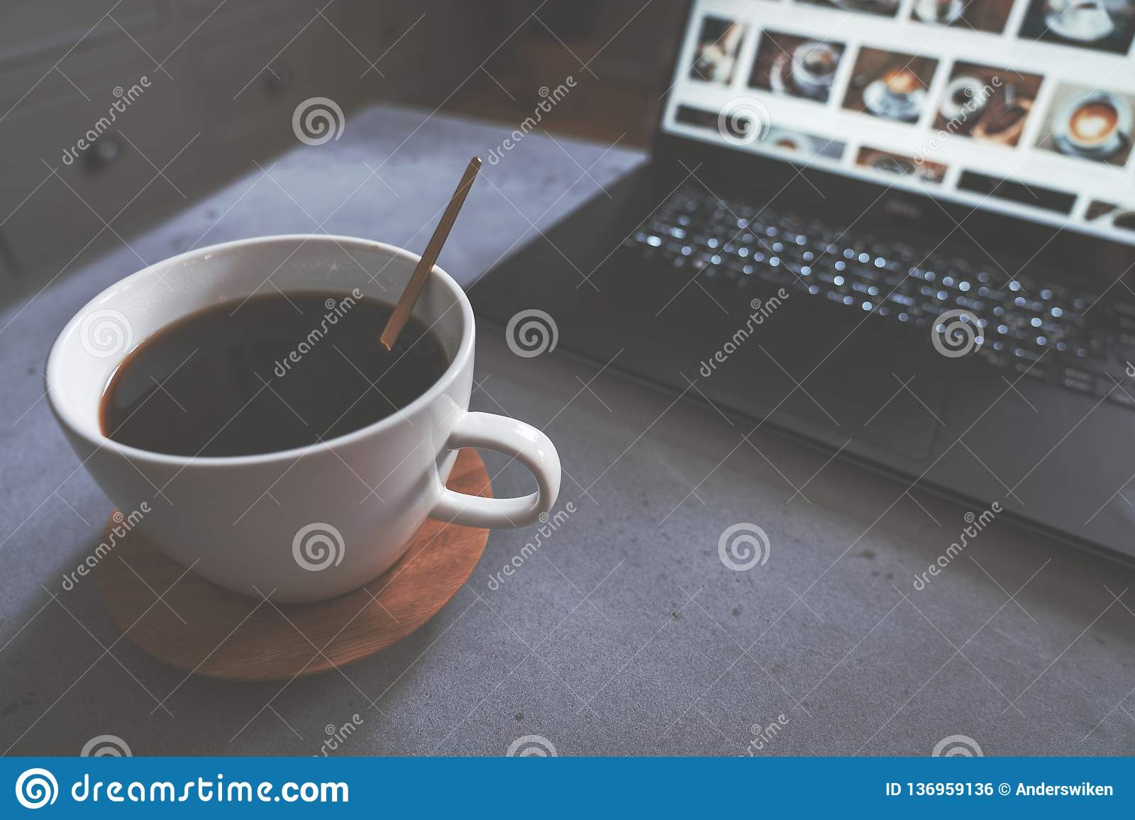 Coffee on concrete table with golden spoon and laptop with coffee pictures as background