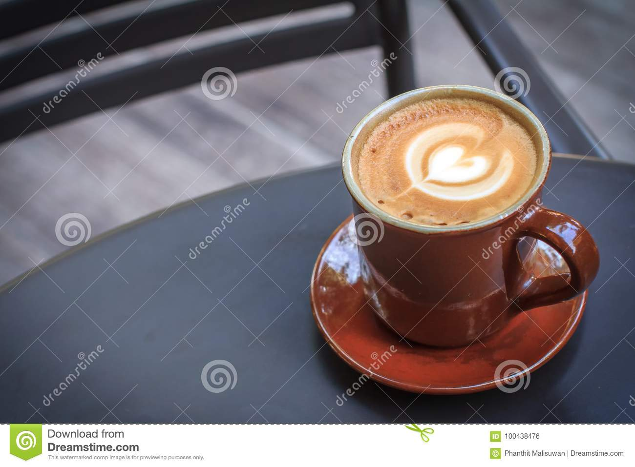 Coffee cup on black metal table in coffee shop with wooden floor background.