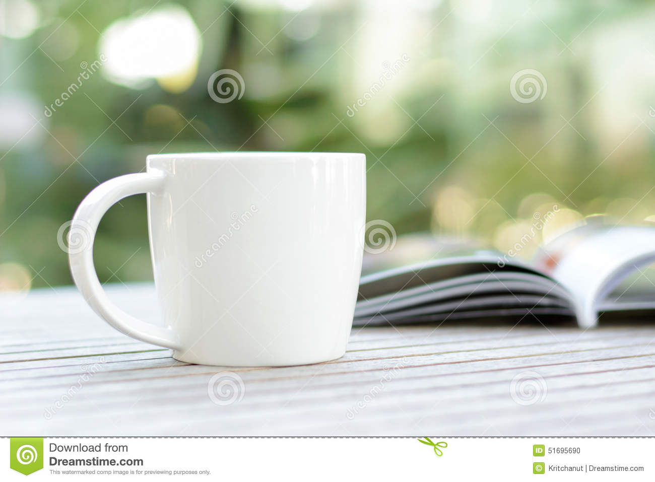 Coffee cup with book on wood table with blur bokeh background