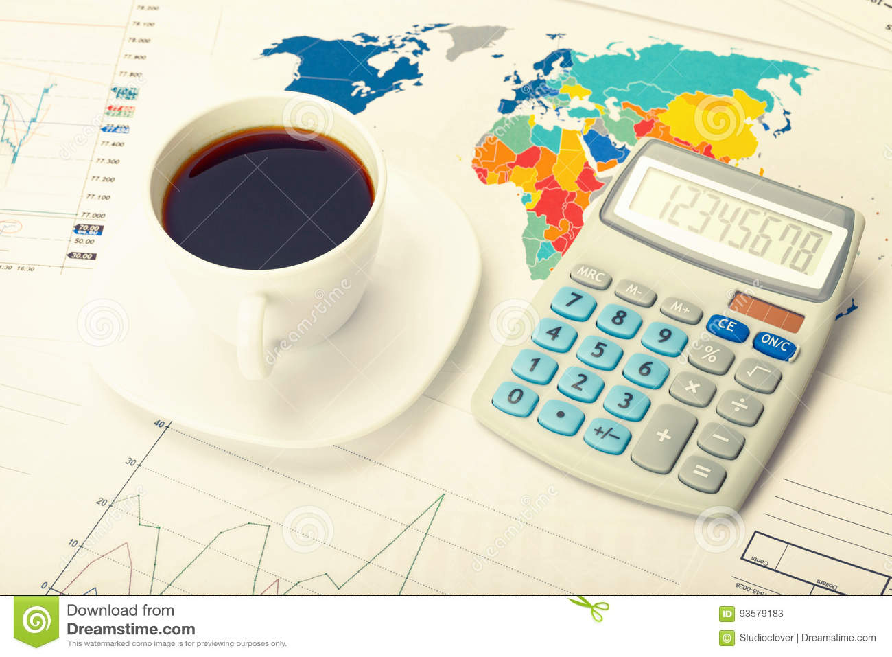 Coffee cup and calculator over world map and some financial charts. Filtered image: cross processed vintage effect.