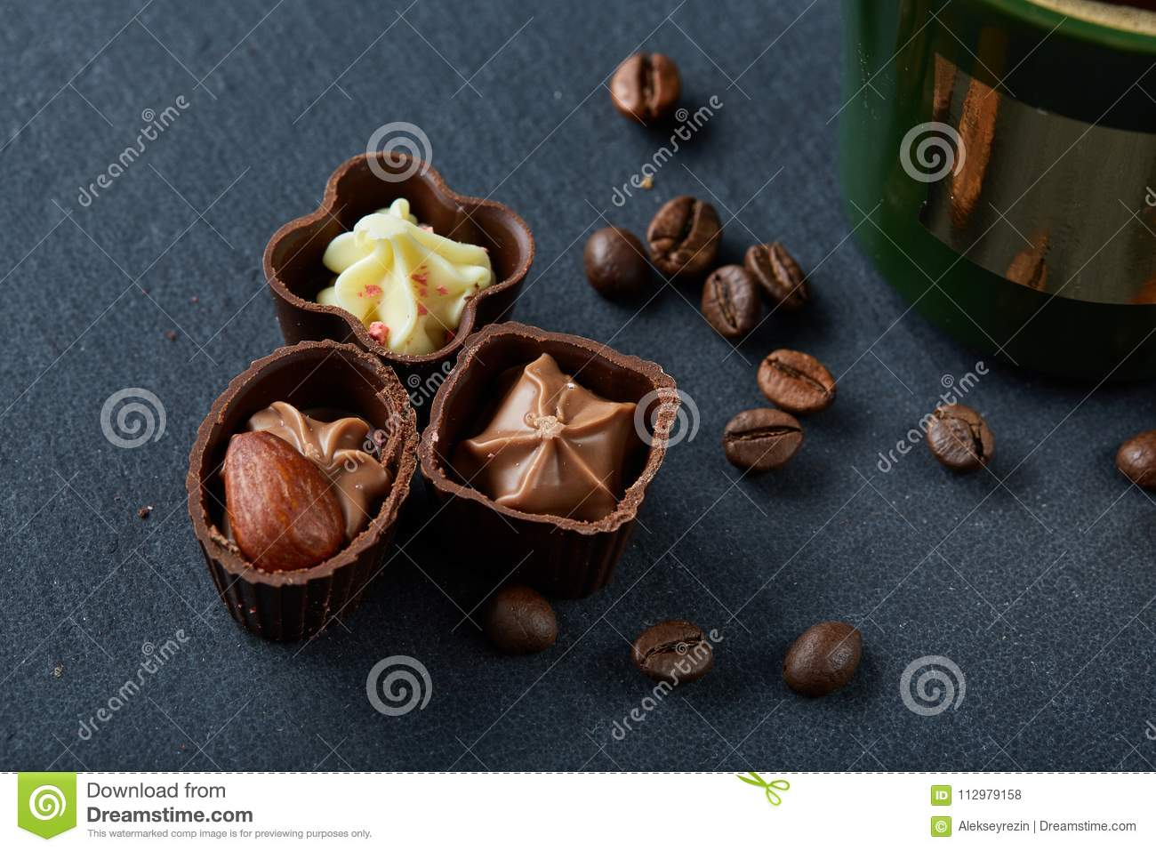 Coffee cup, coffee beans, chocolate candies on stone board over wooden background, selective focus, close-up
