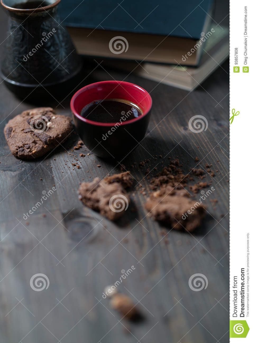 Coffee Cup and cookies are next to the stack of books