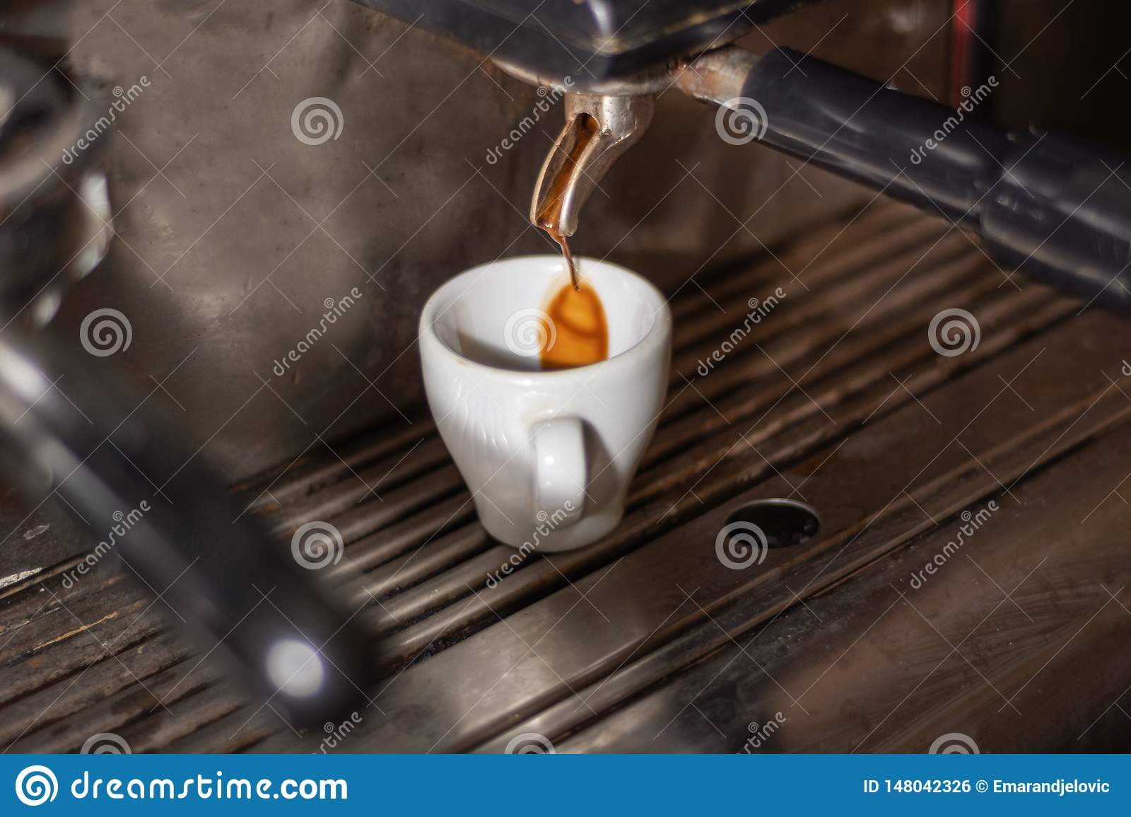Coffee cup on an espresso machine and coffee drip in a cup