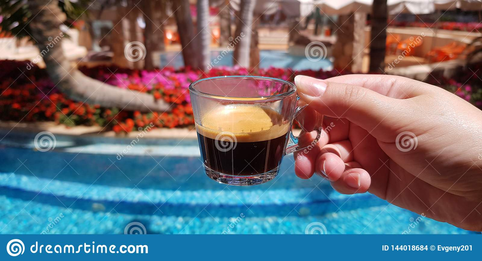 Coffee cup made from transparent glass in female hand against blue outdoor pool