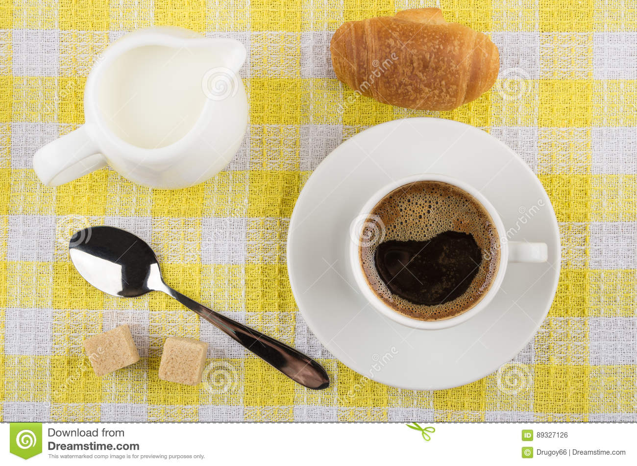Coffee cup, milk jug, croissant, sugar and spoon on napkin