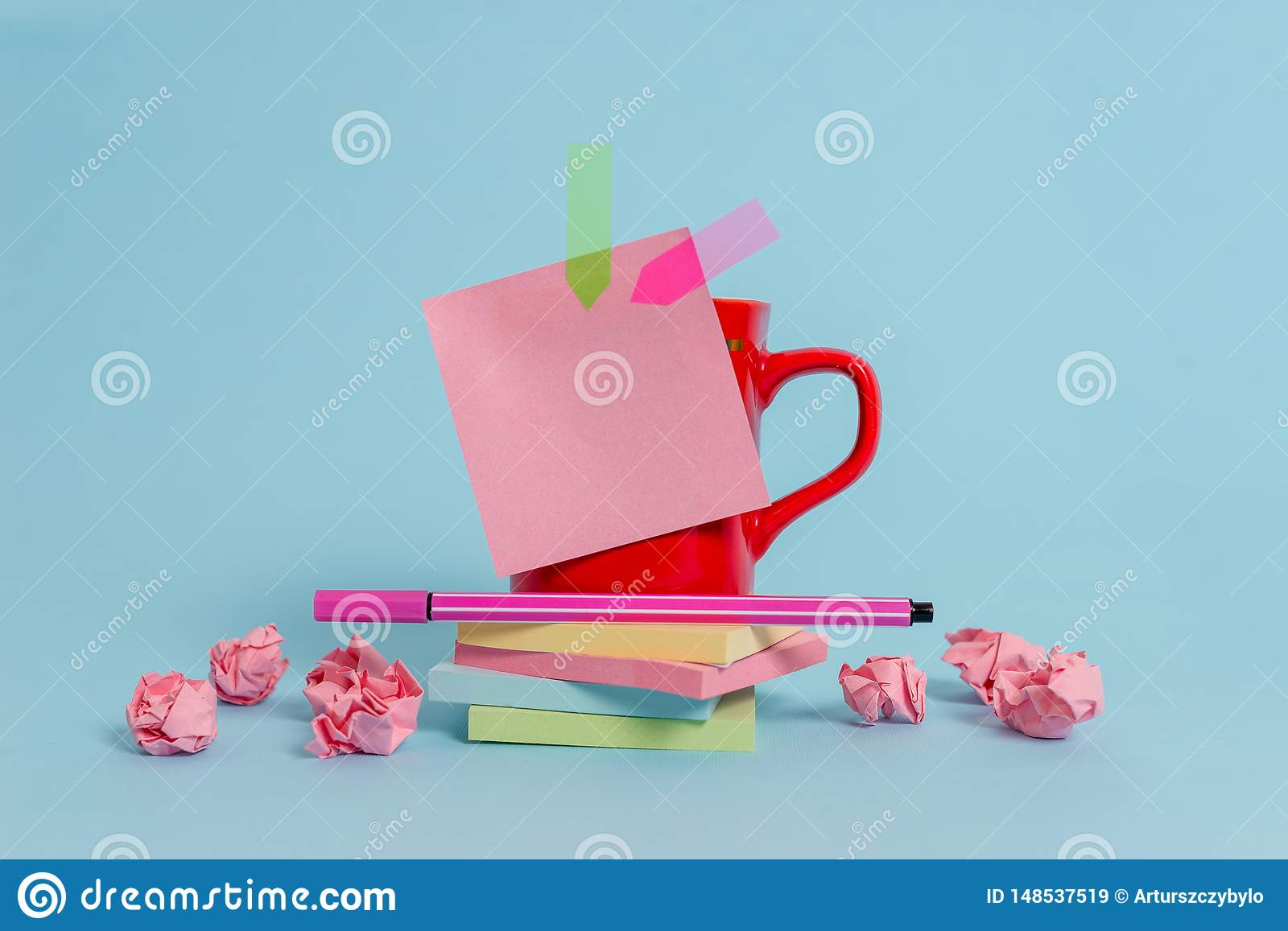 Front view coffee cup colored sticky note arrow banners crushed paper balls stacked pads pen lying beautiful pastel