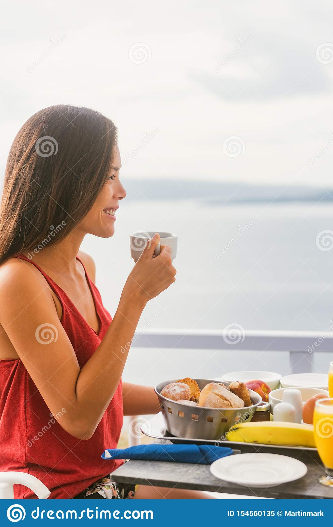 Coffee drink happy Asian woman drinking tea cup on morning breakfast outside in sun enjoying food at hotel restaurant or cruise
