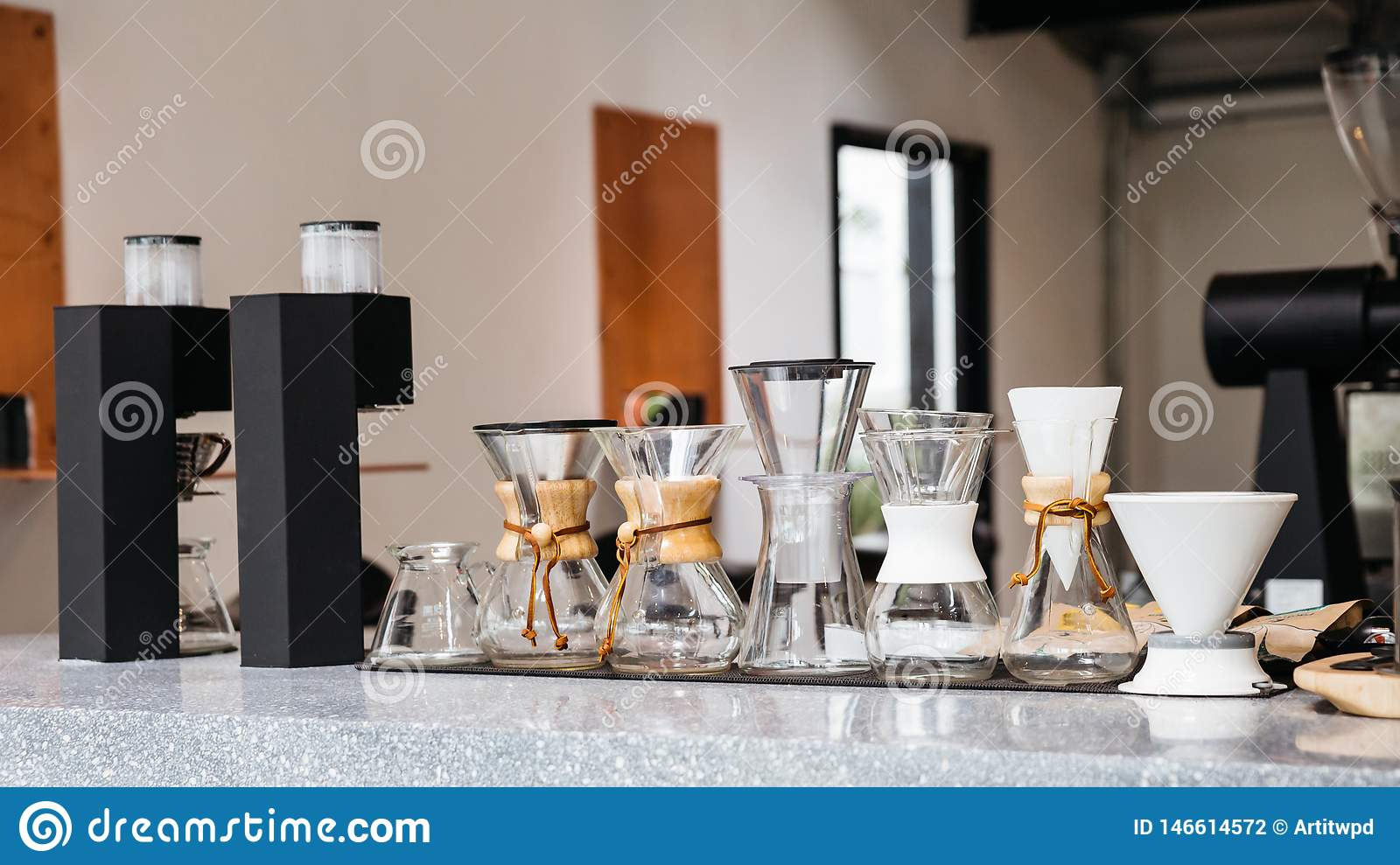 Coffee equipments with various sizes of drip coffee cups, drip paper and Espresso machine on marble top counter