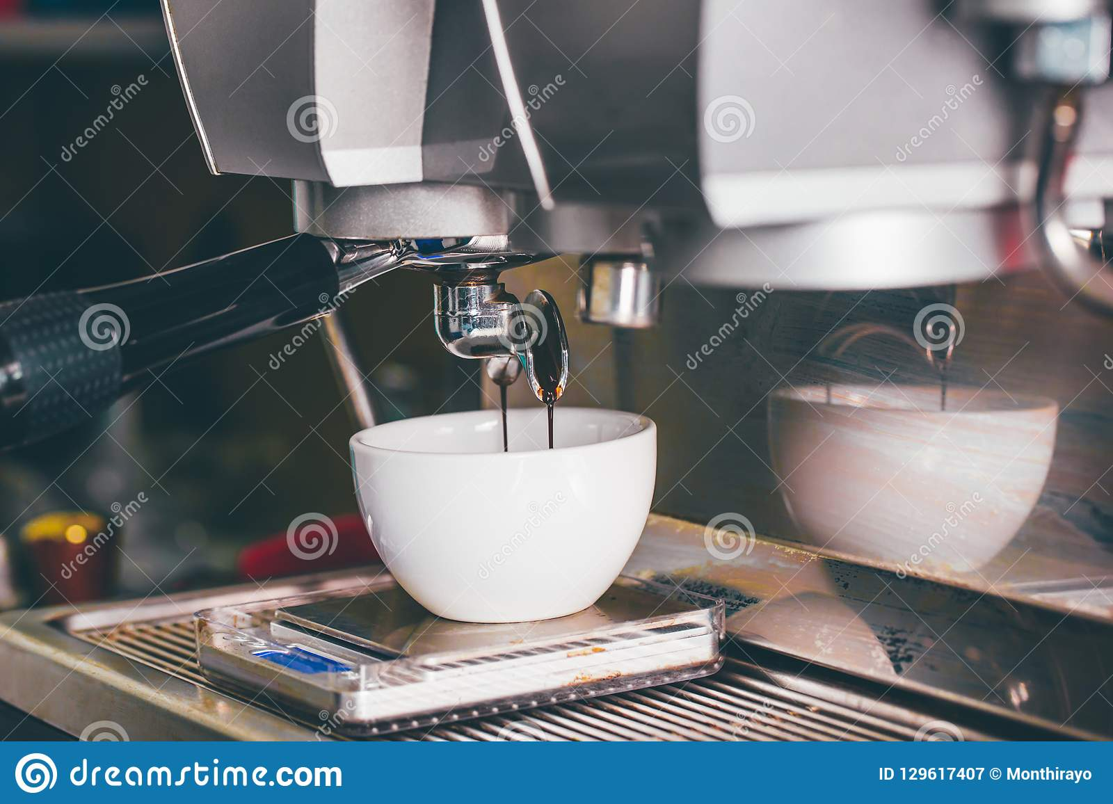 Coffee extraction pouring into a cup from professional coffee ma