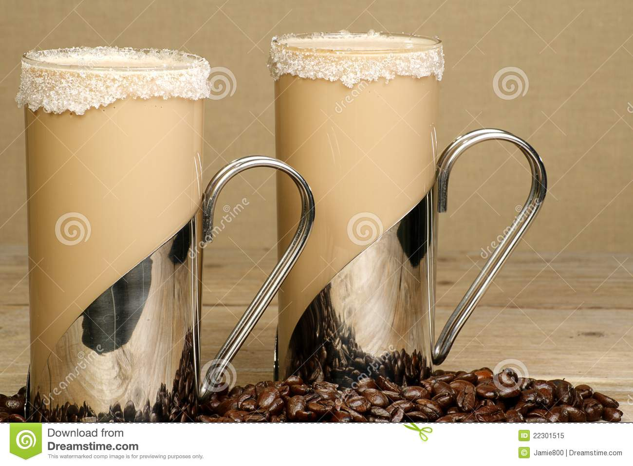 Two mugs of iced coffee frappe with coffee beans on a wooden table.