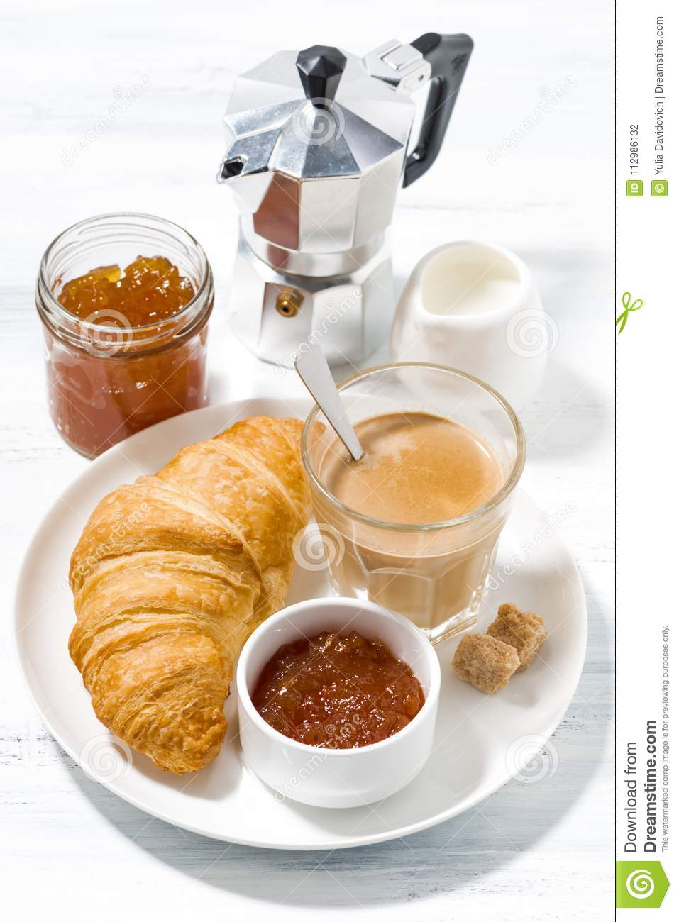 Coffee with milk and croissants with jam for breakfast, vertical