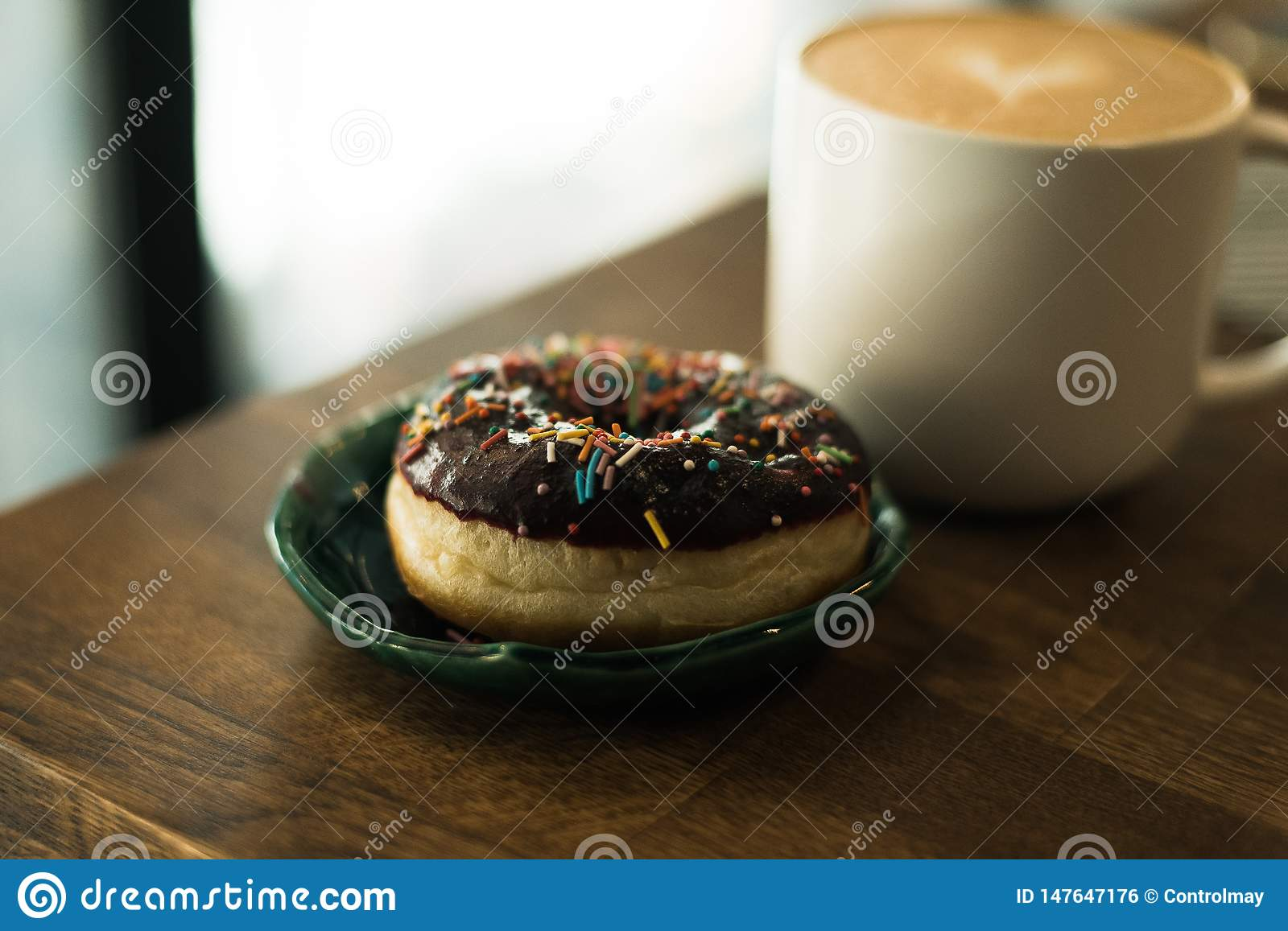 Coffee with a milk and a donut
