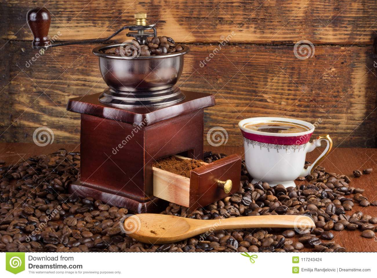 Coffee mill grinder and cup of coffee and wooden spoon on old retro background with roasted beans