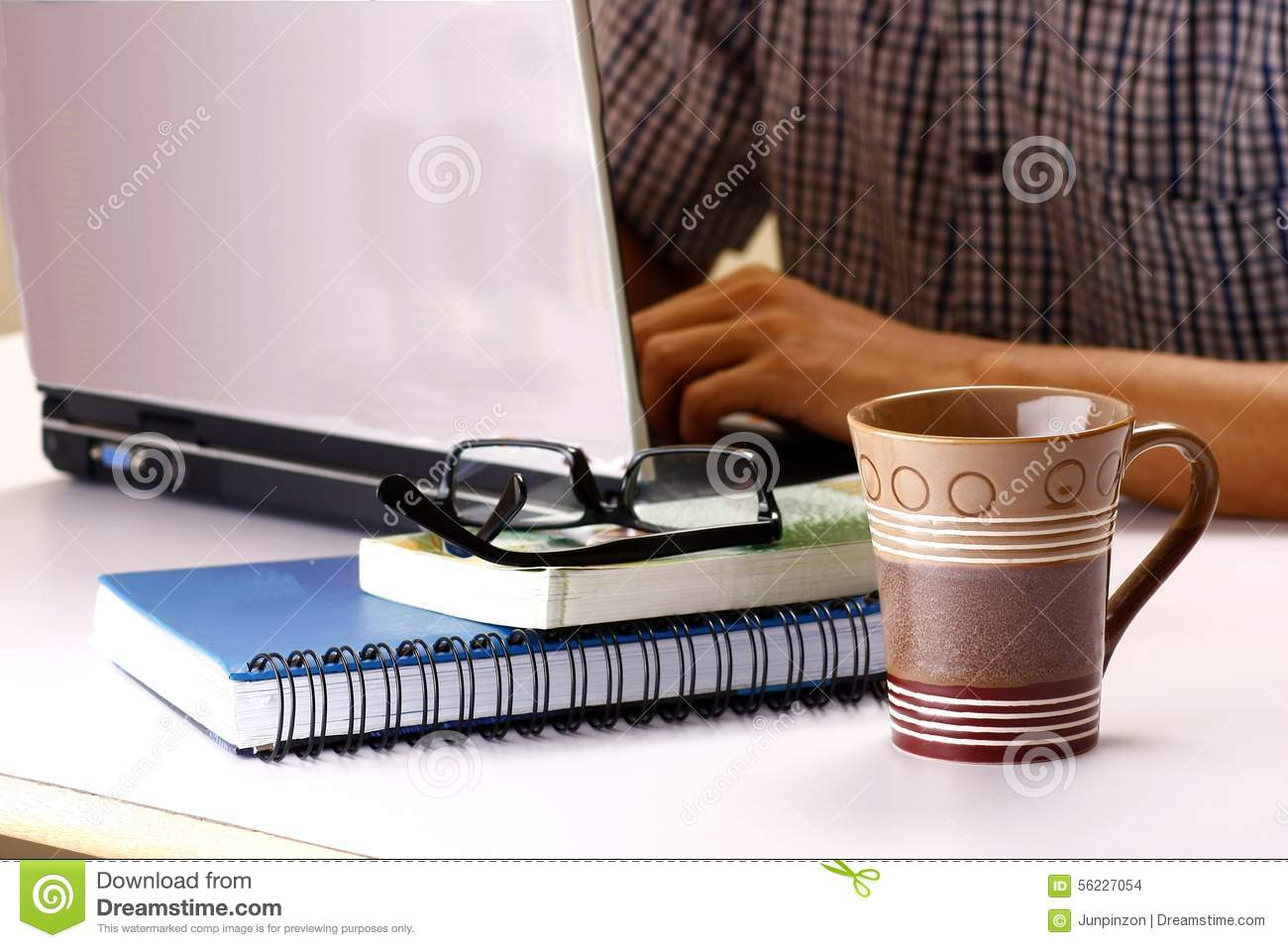 Coffee Mug Stack Of Books And Man Working On A Laptop
