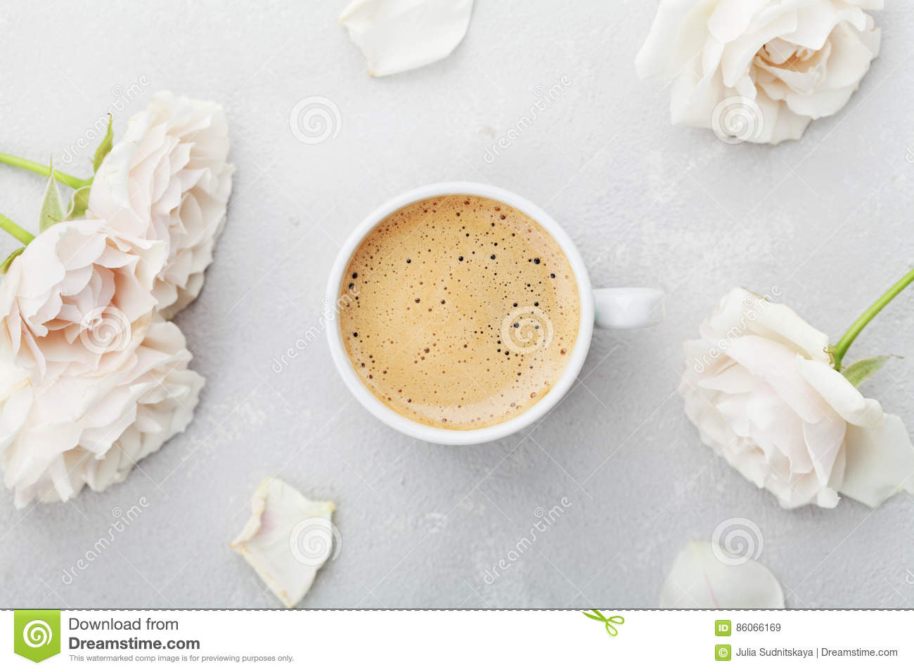 Coffee mug and vintage rose flowers for good morning on gray stone table from above in flat lay style. Beautiful breakfast.