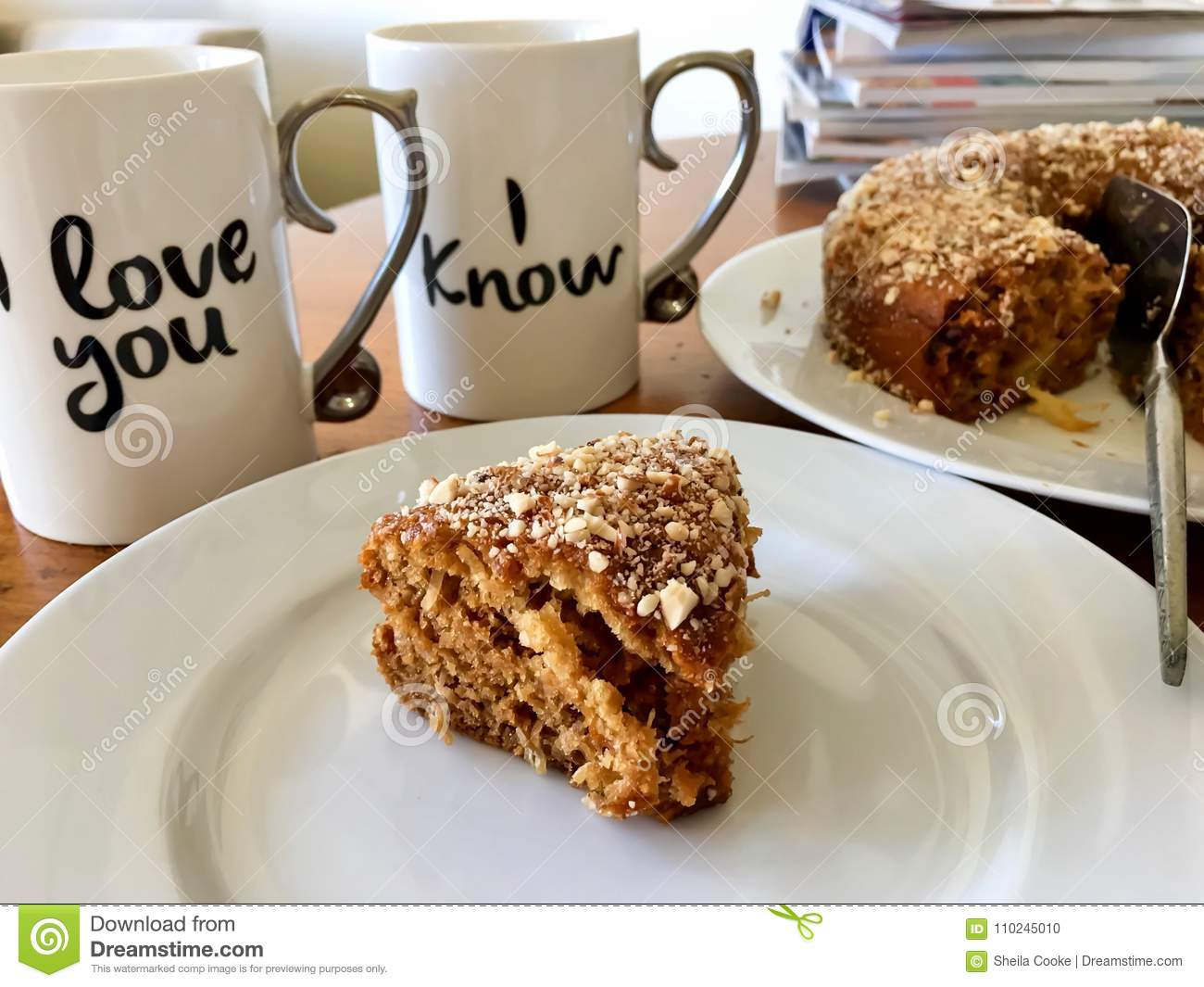 Coffee mugs with love messages beside homemade cake
