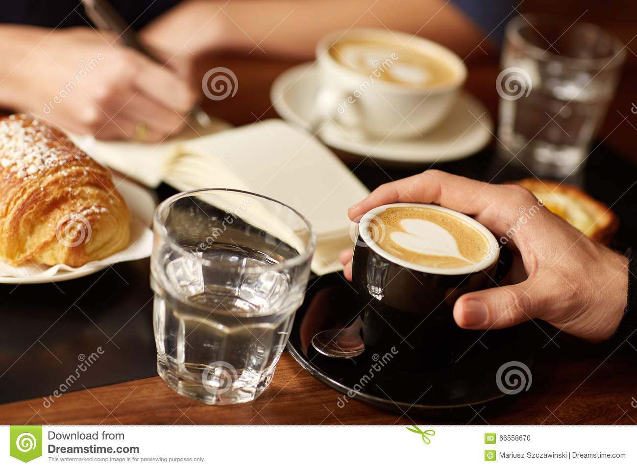 coffee shop table with hands espresso and someone writing stock