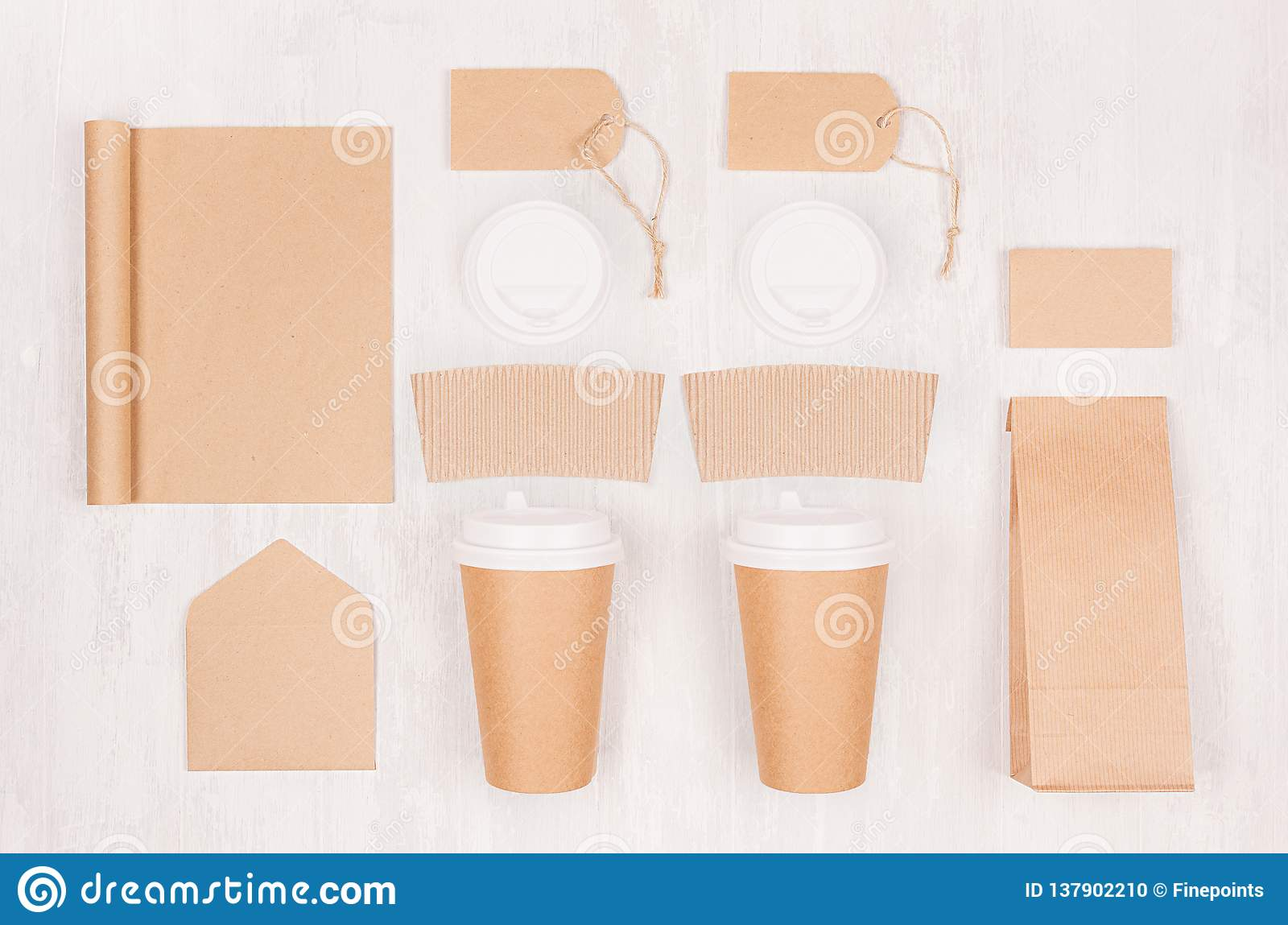 Coffee shop template for branding identity - two brown paper cups with blank notebook, packet, label, card, cap, envelope on wood.