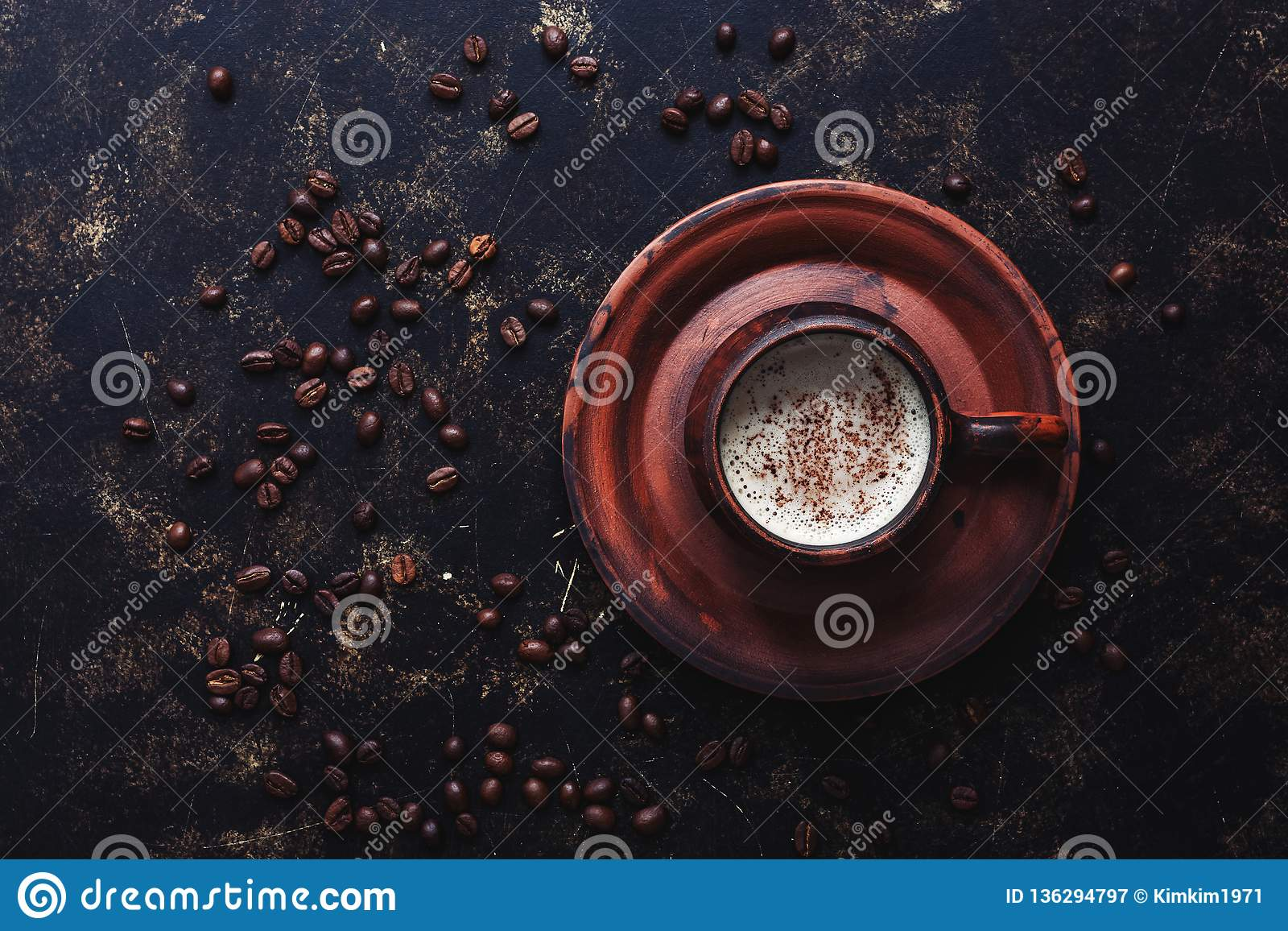 Coffee in a vintage brown ceramic cup on a dark grunge background with roasted coffee beans. Top view, copy space