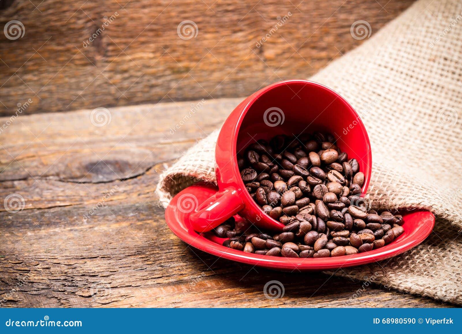Coffeecup y placa rojos con los coffeebeans derramados