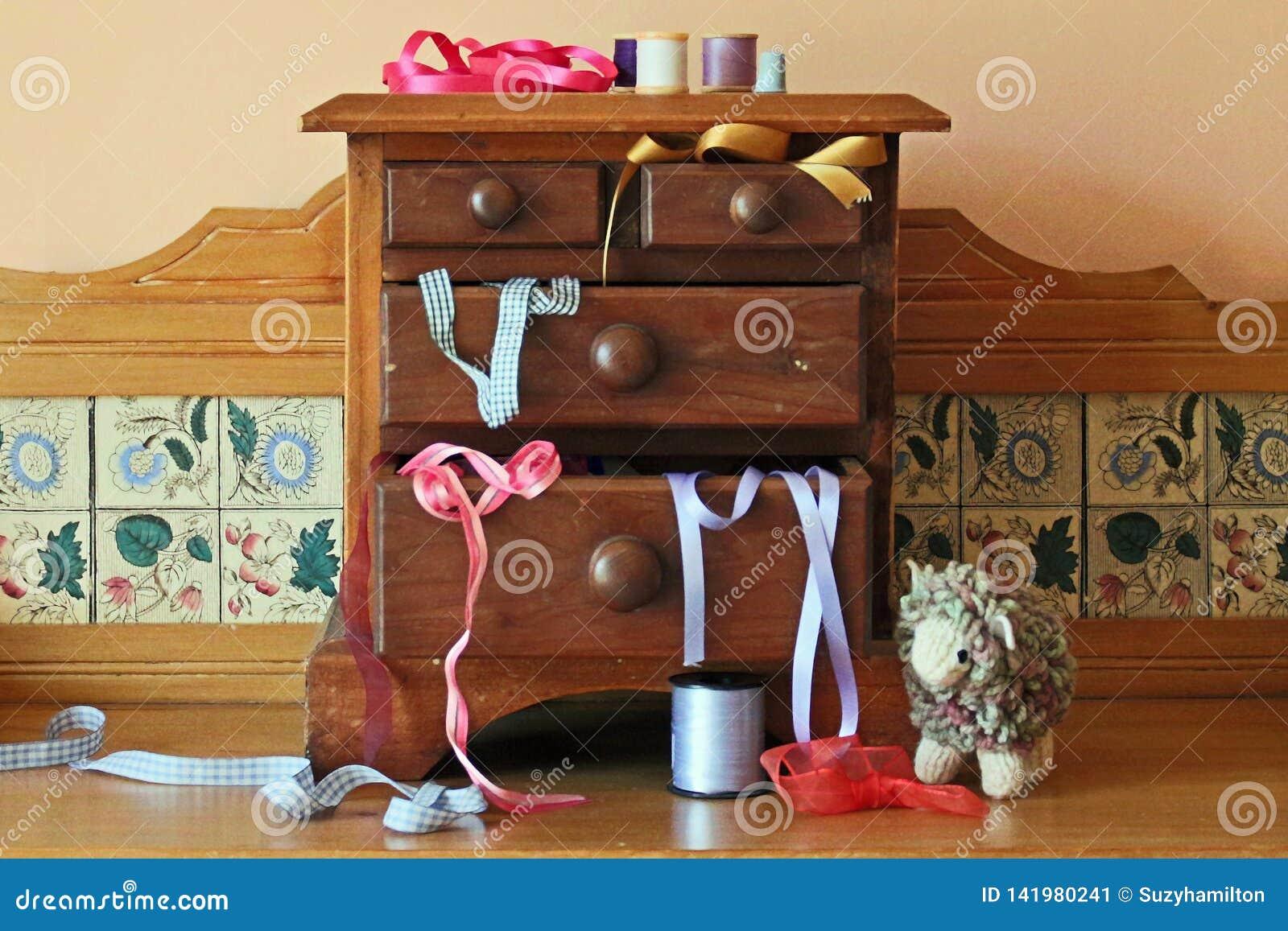 Coffre des tiroirs miniature en bois avec les ustensiles de couture l entourant