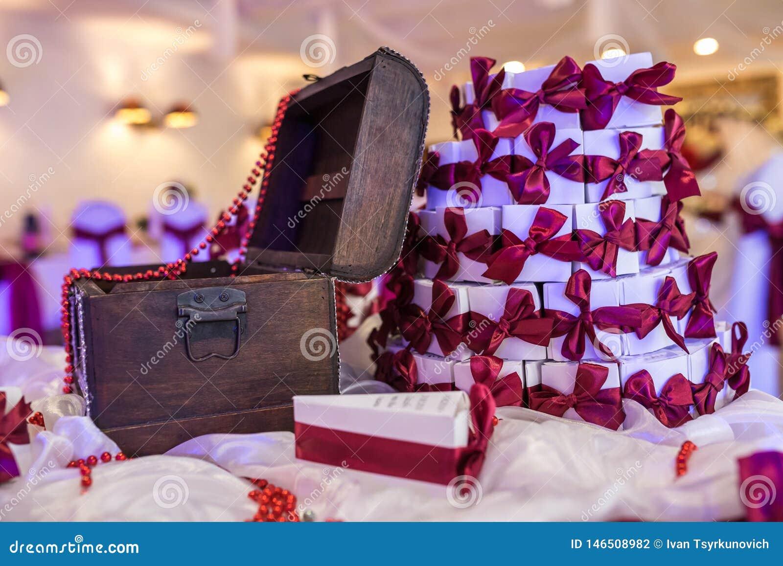 Coffre en bois sur la table avec une nappe violette et de petits cadeaux pour des invités des nouveaux mariés