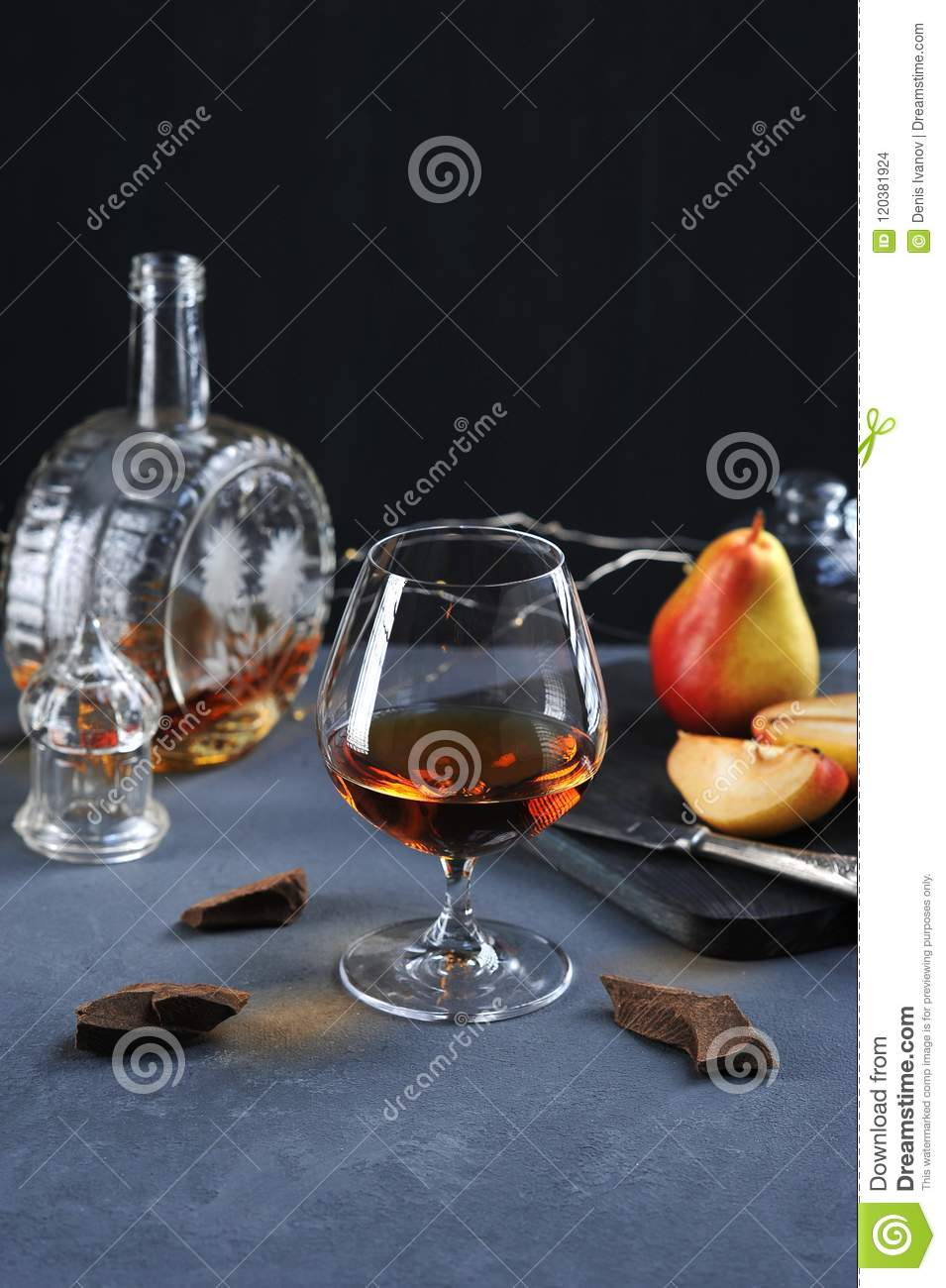 Cognac in a glass with chocolate and pear