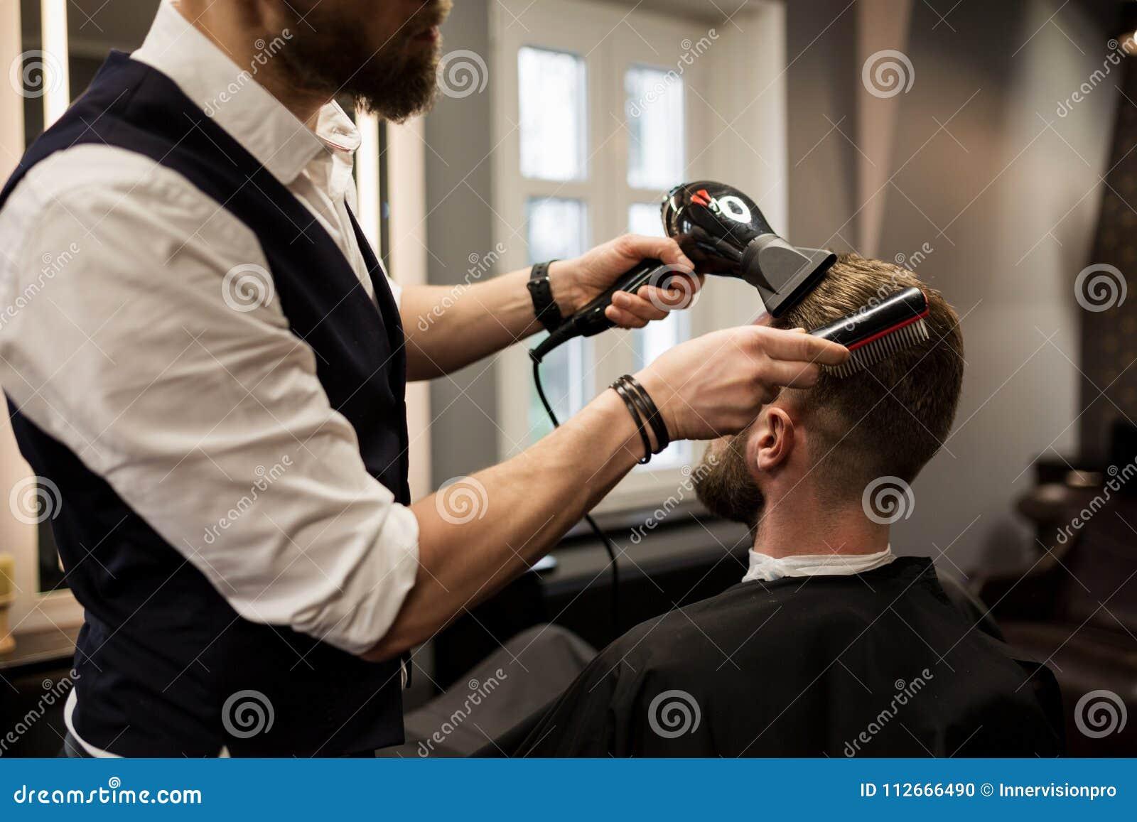 Coiffeur dénommant des cheveux de client avec le dessiccateur