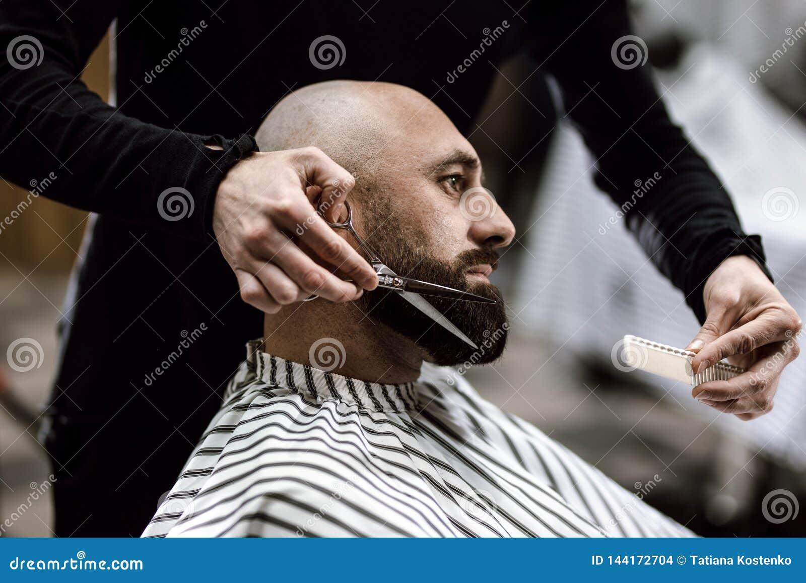 Coiffeur de mode habillé dans une barbe noire de ciseaux de vêtements d homme brutal dans le raseur-coiffeur élégant