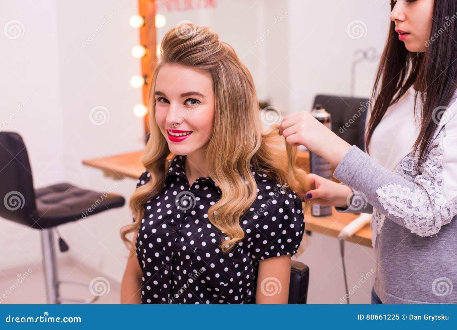 Coiffeur Féminin Tenant Et Faisant La Coiffure à La Belle Jeune ...