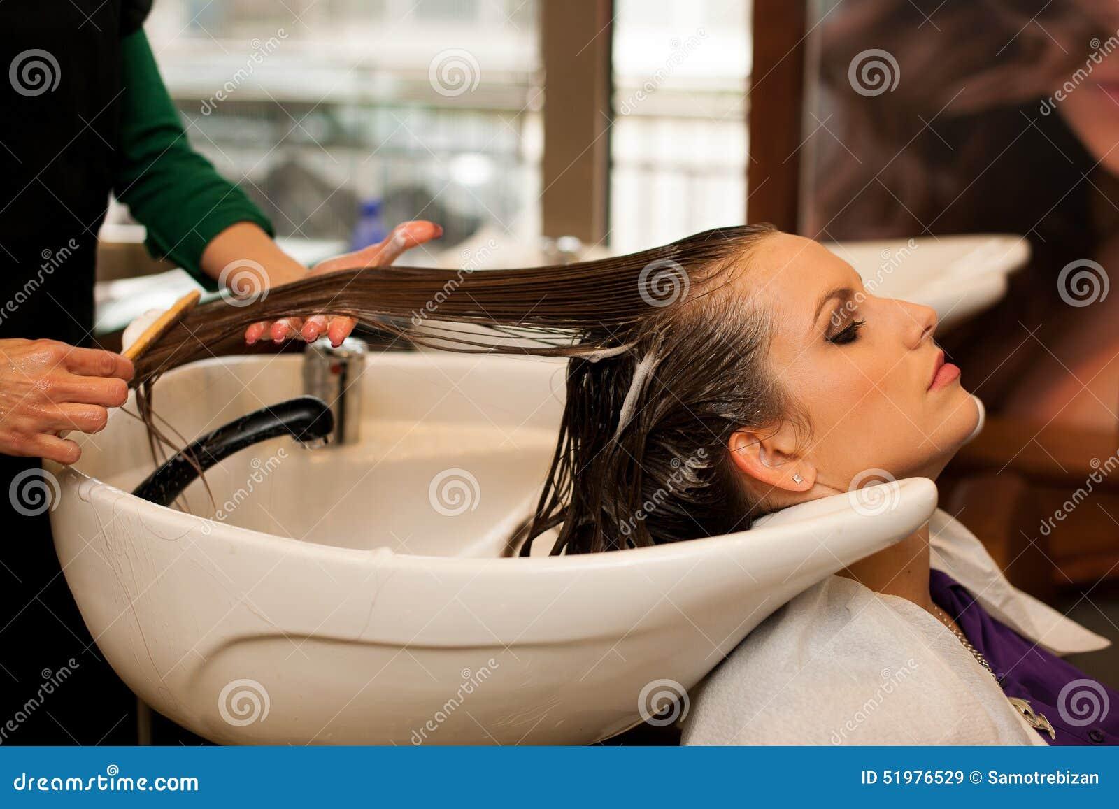 Coiffeur faisant le traitement de cheveux à un client dans le salon