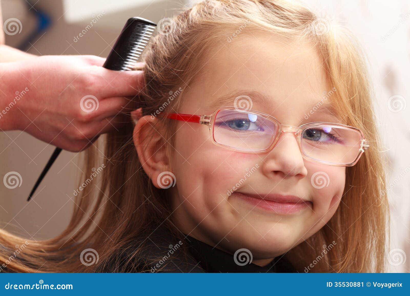 coiffeur peignant l 39 enfant de petite fille de cheveux dans. Black Bedroom Furniture Sets. Home Design Ideas