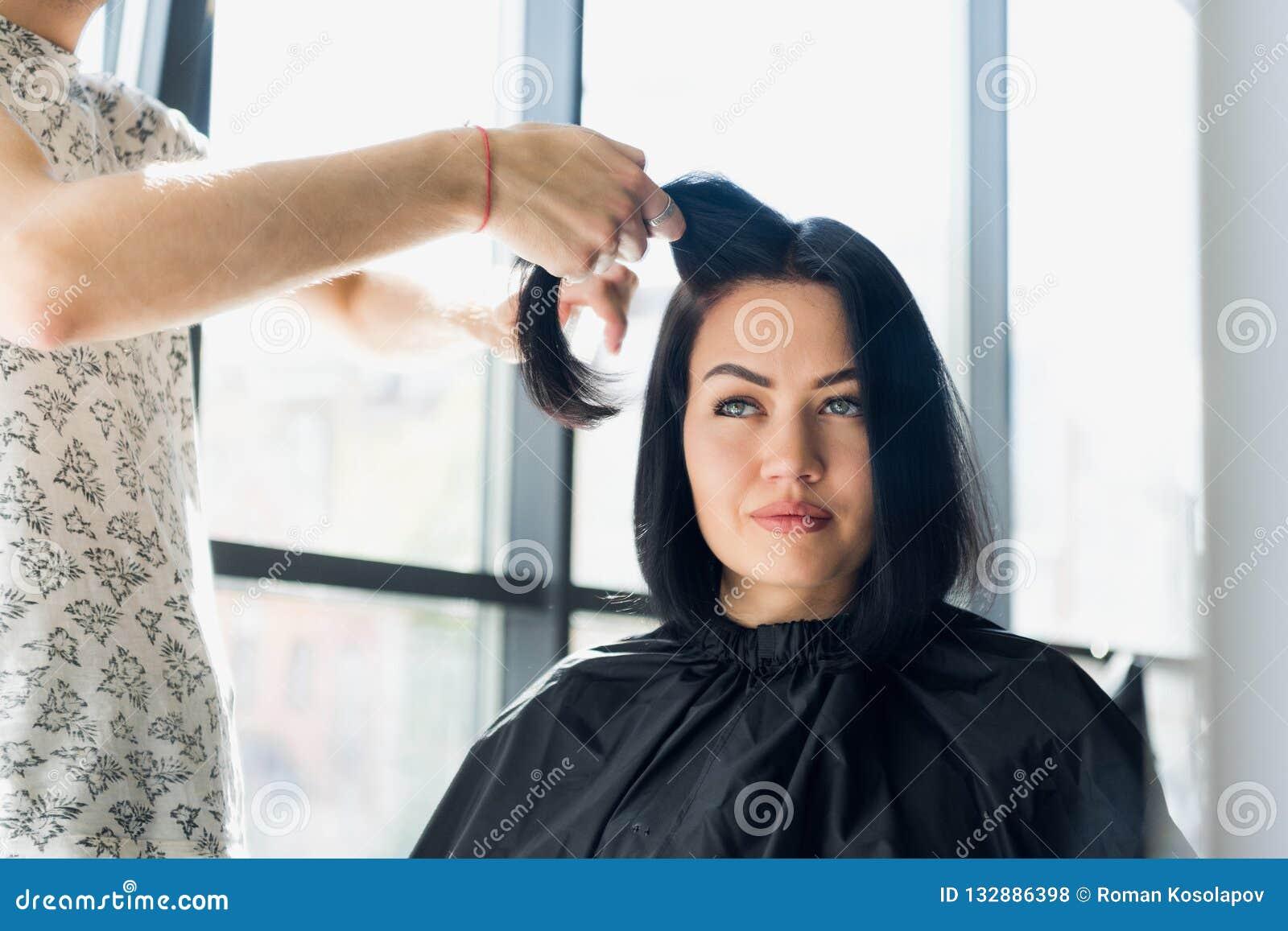 Coiffeur professionnel travaillant avec les cheveux du client dans le salon Traction d un brin