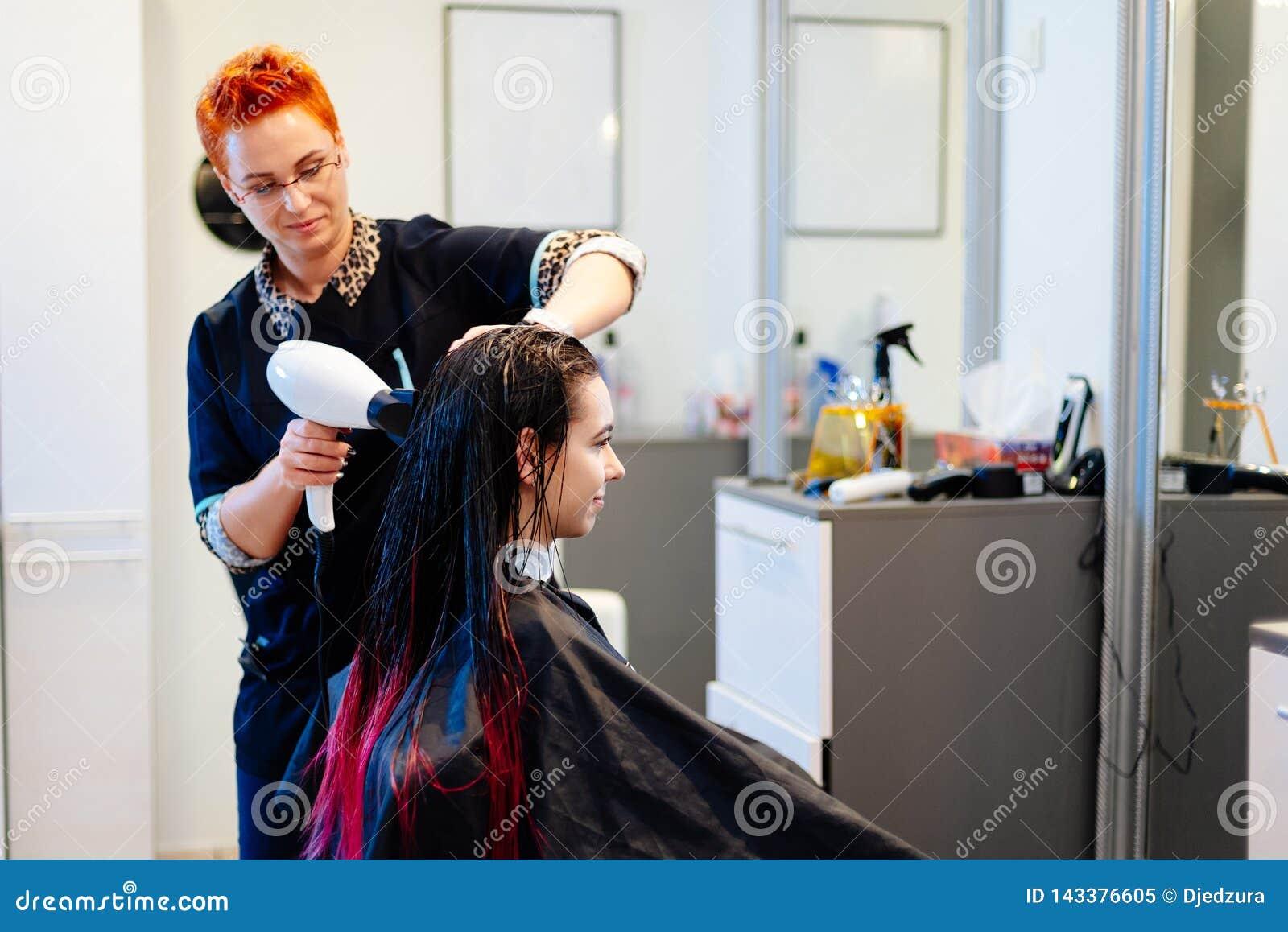 Coiffeur séchant les cheveux femelles de client avec le dessiccateur de main dans le salon de coiffure