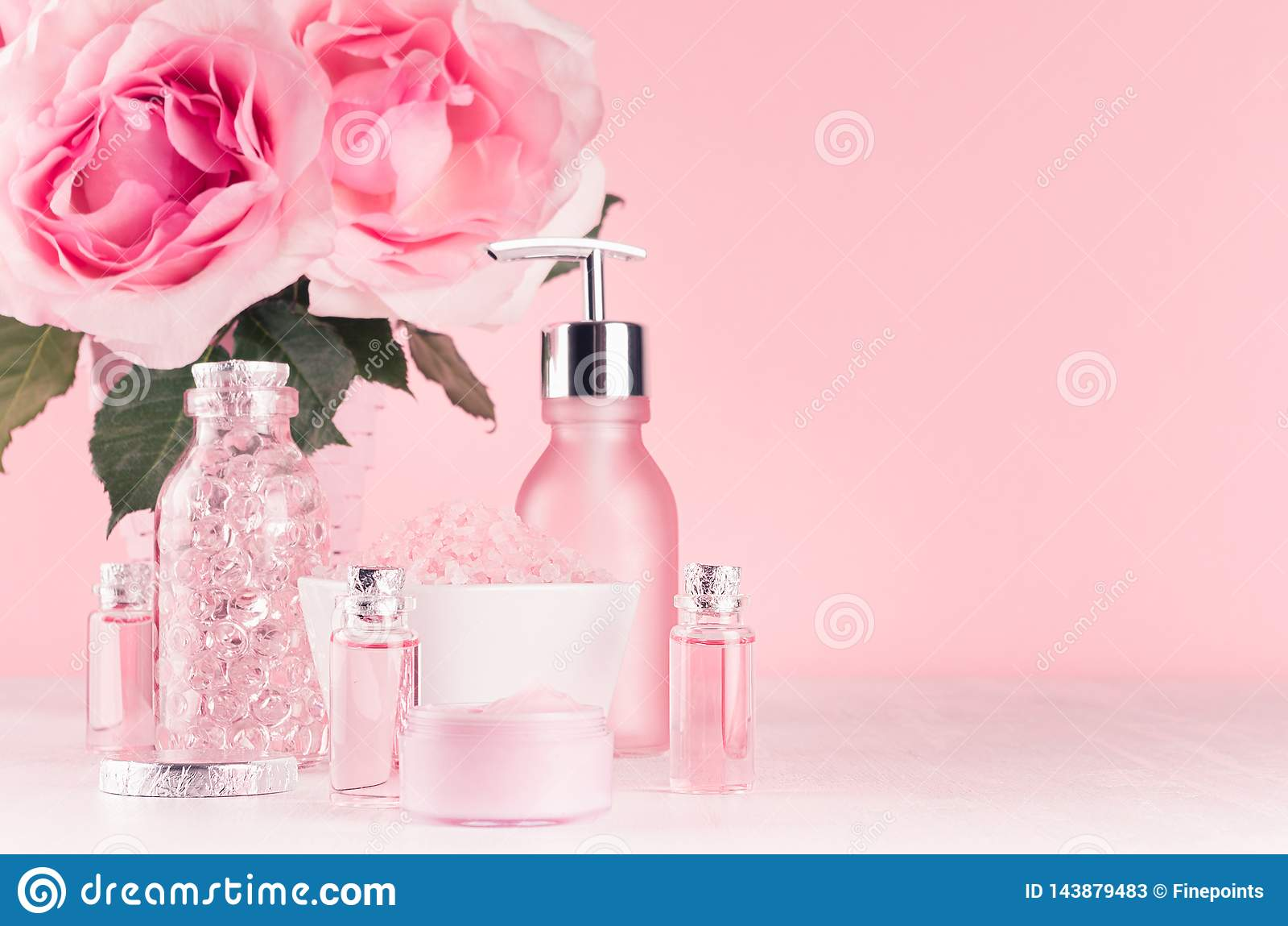 Coiffeuse de fille douce avec des fleurs, produits de cosmétiques - s est levée l huile, sel de bain, crème, parfum, serviette de
