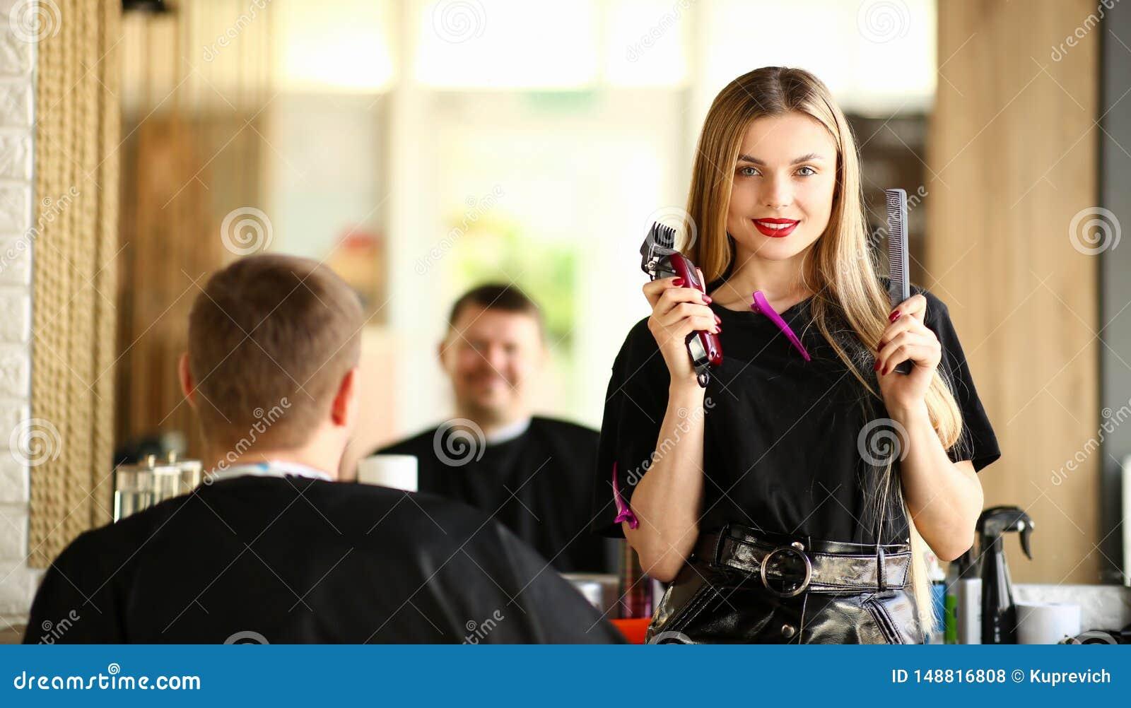 Coiffeuse Showing Razor de femme et peigne au client