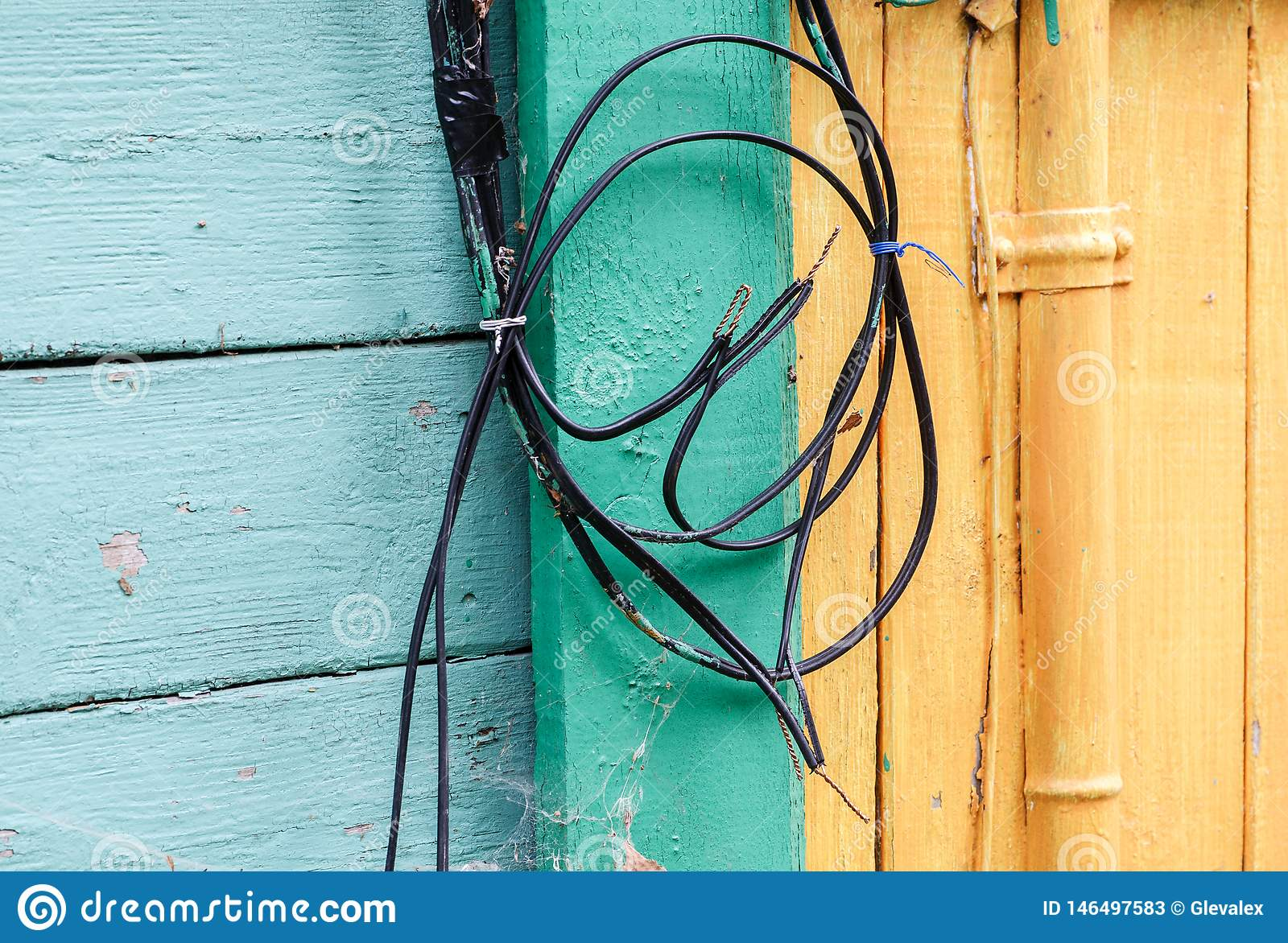 Coiled Black Wires On The Wall Of Colored Wooden House Stock ... on