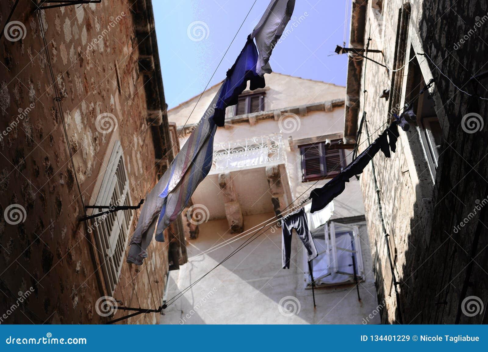 Coin de la rue déprimé avec de vieilles maisons urbaines avec la blanchisserie accrochant entre les bâtiments - la mer Méditerran