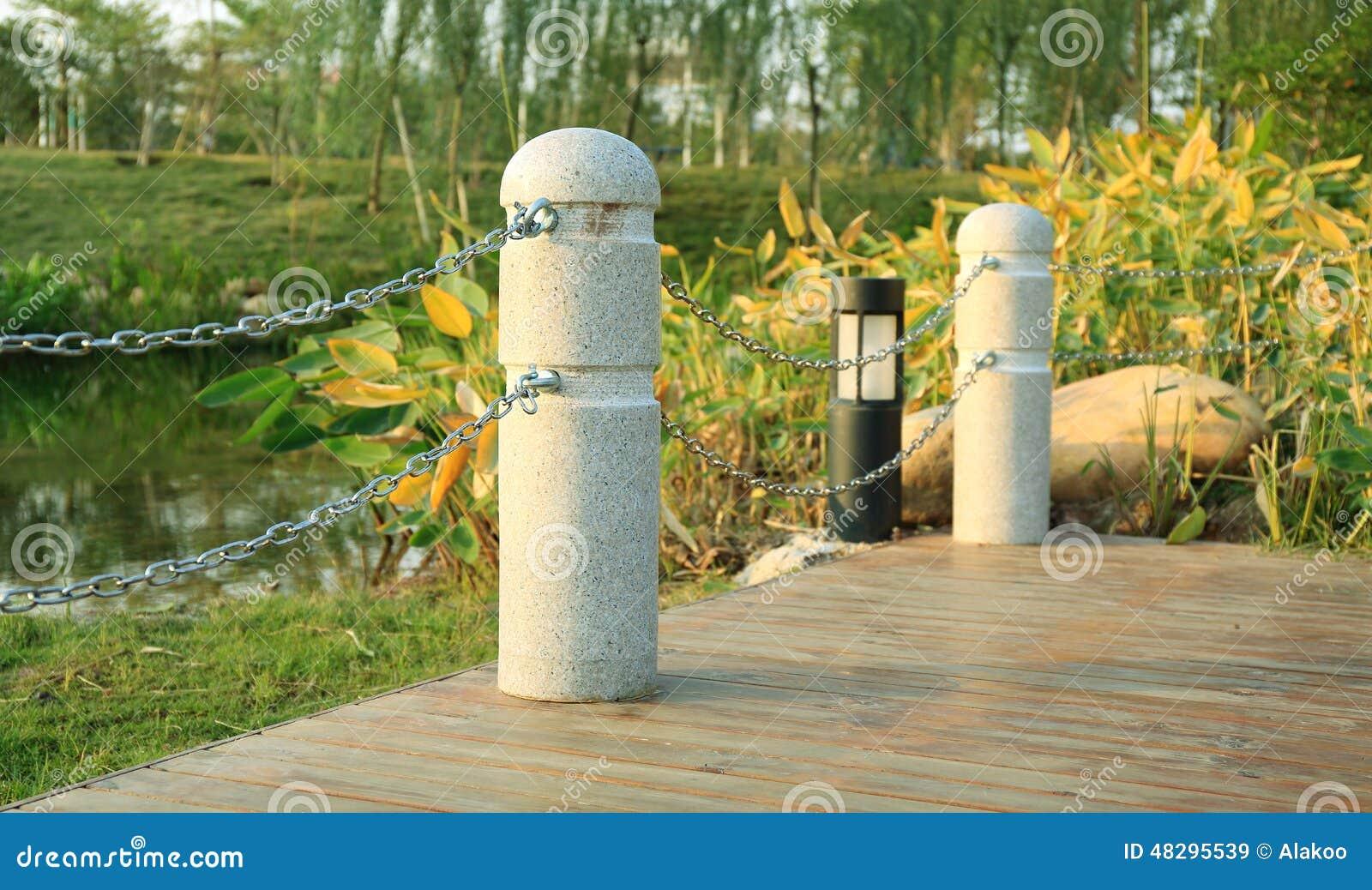 Coin de plate-forme en bois avec les barrières en pierre par la rivière