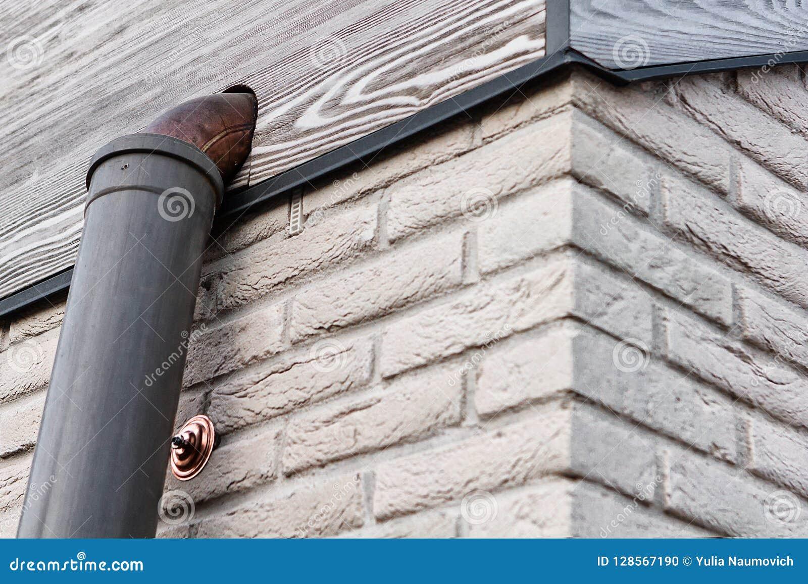 Coin du mur de briques blanc avec le conseil frontal en bois gris et du tuyau de cuivre pendant la construction