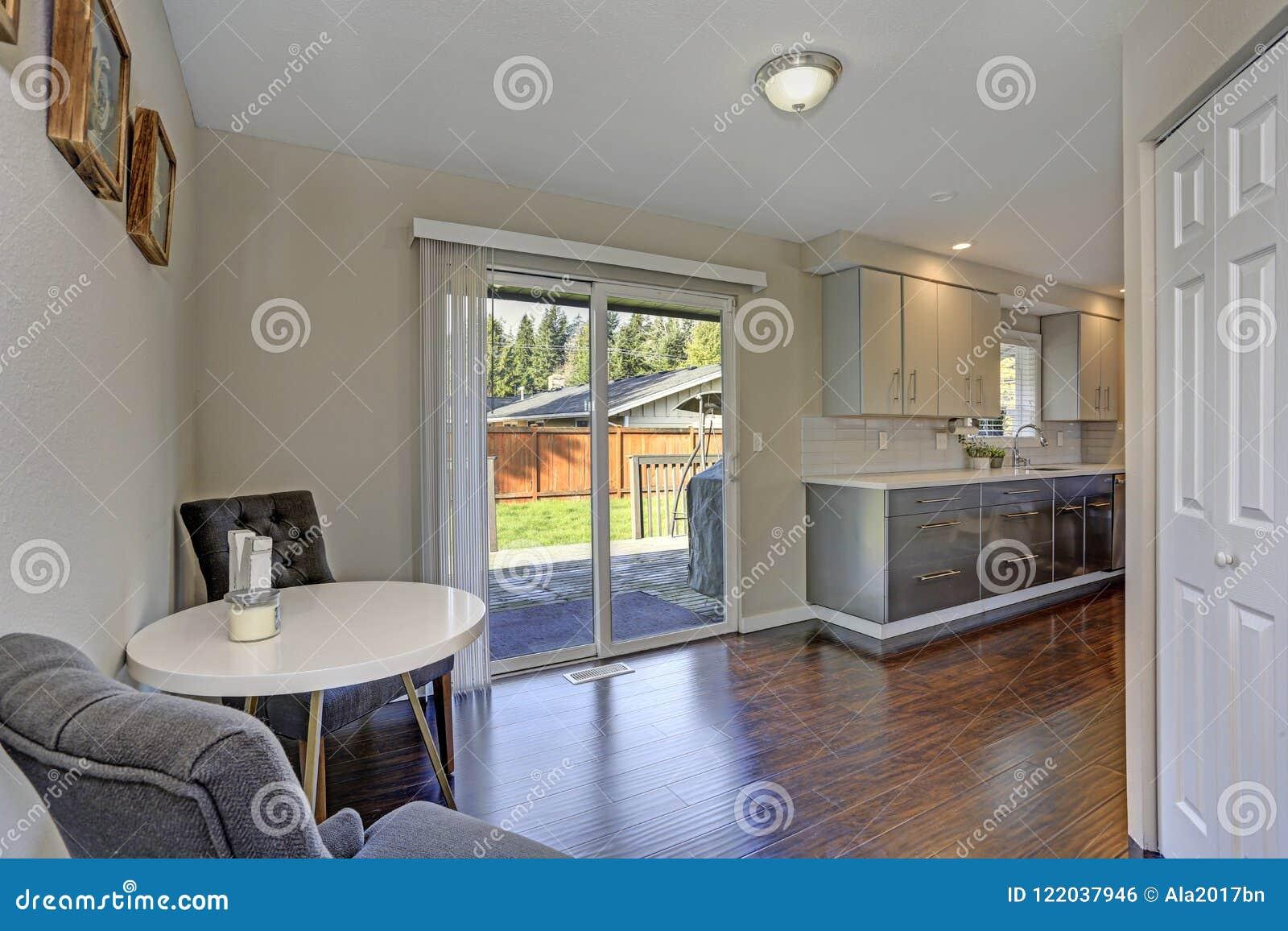 Coin-repas avec le plancher en bois dur et la sortie polis à un patio