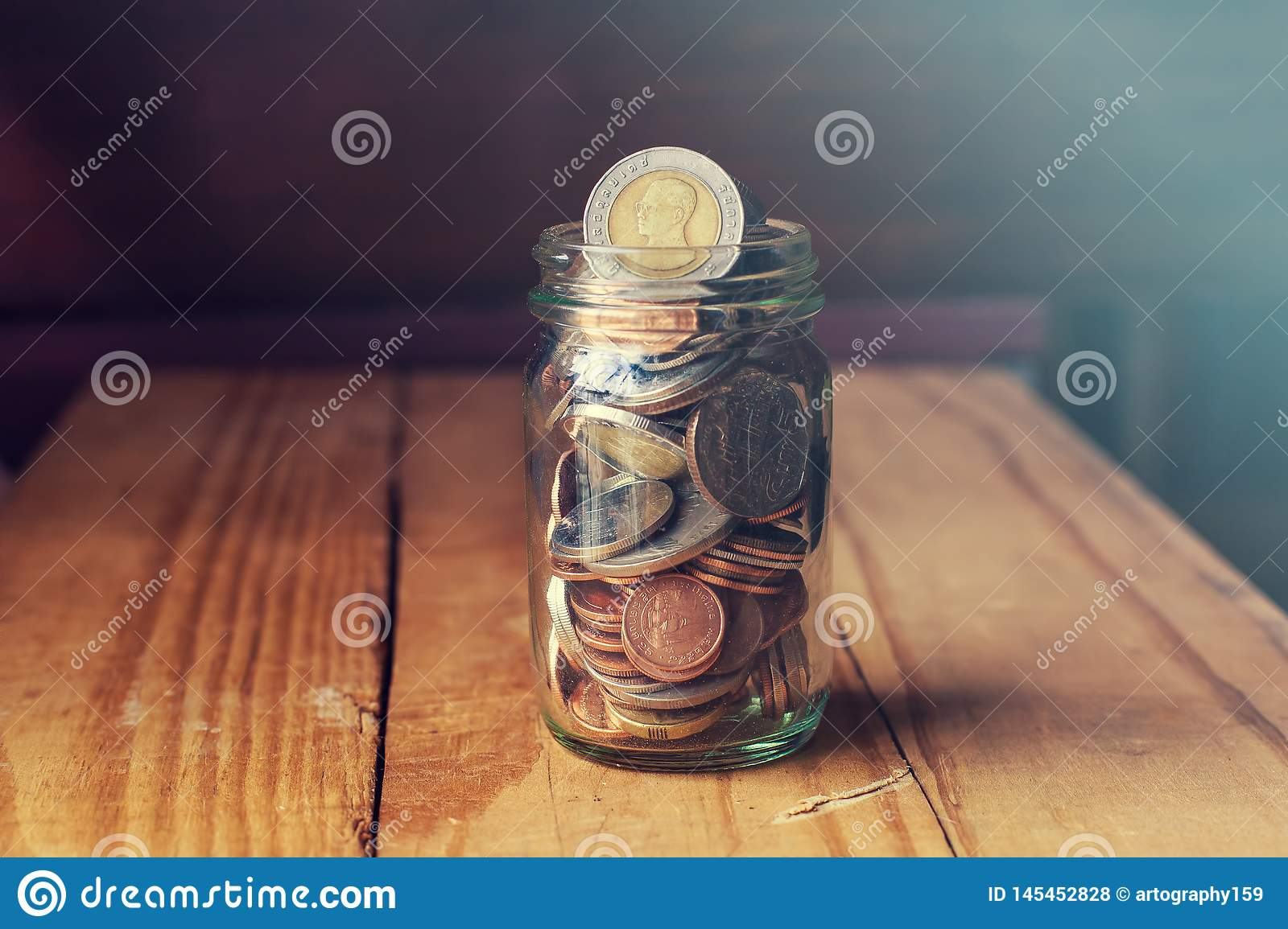 Coins in glass jar on wood table, Saving money concept.