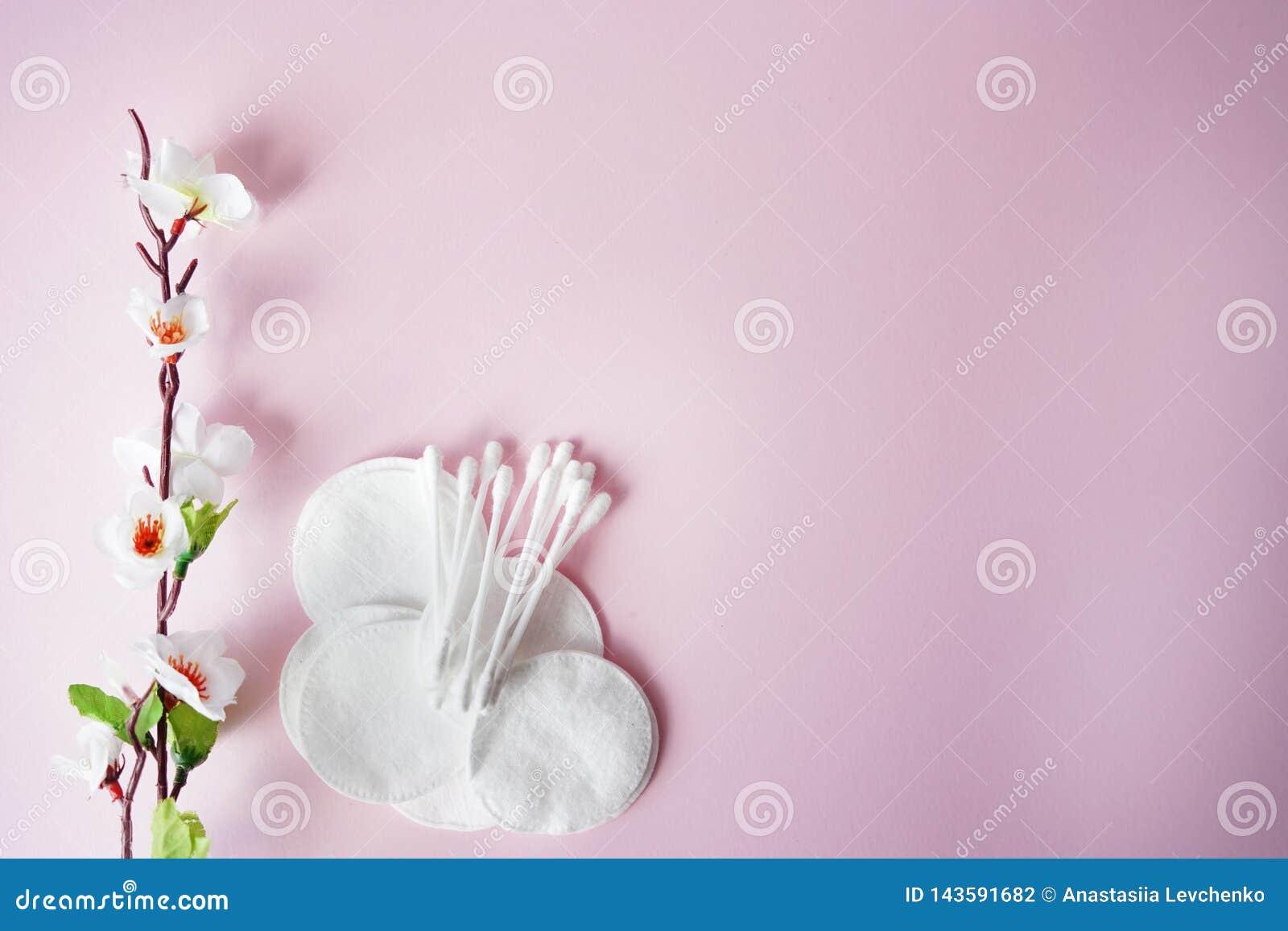 Cojines y esponjas de algod?n con las flores en fondo en colores pastel rosado Copie el espacio Lugar para el texto