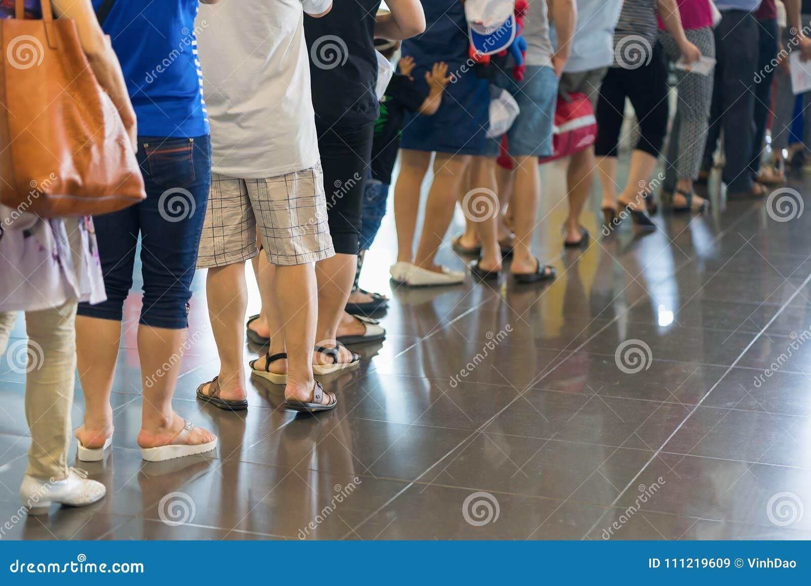 Cola del primer de la gente asiática que espera en la puerta de embarque en el aeropuerto