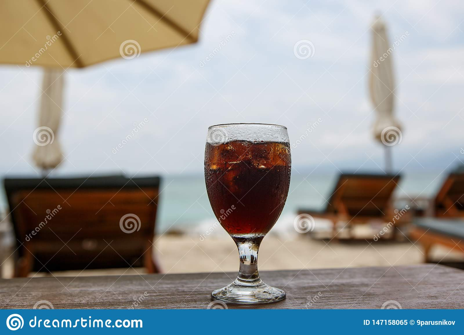 Cola glass on beach with umbrellas. Cooling drink