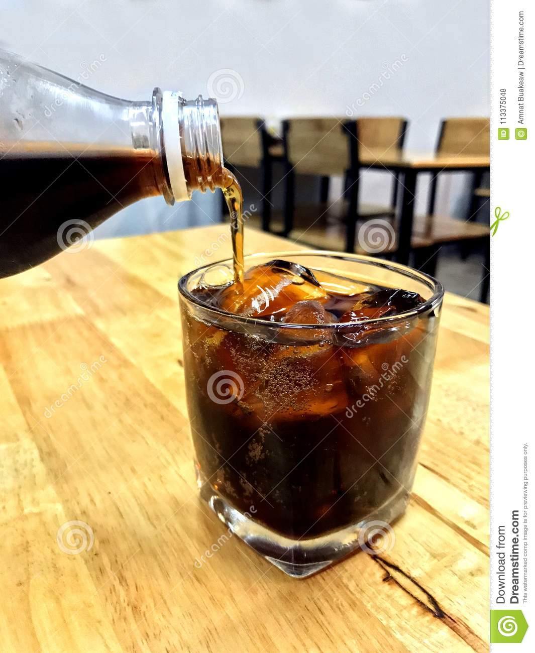 Cola in glass ice, Pouring cola from glass bottles drinks to a glass with ice cubes, cola in glass ice beverage Drinks on the rest