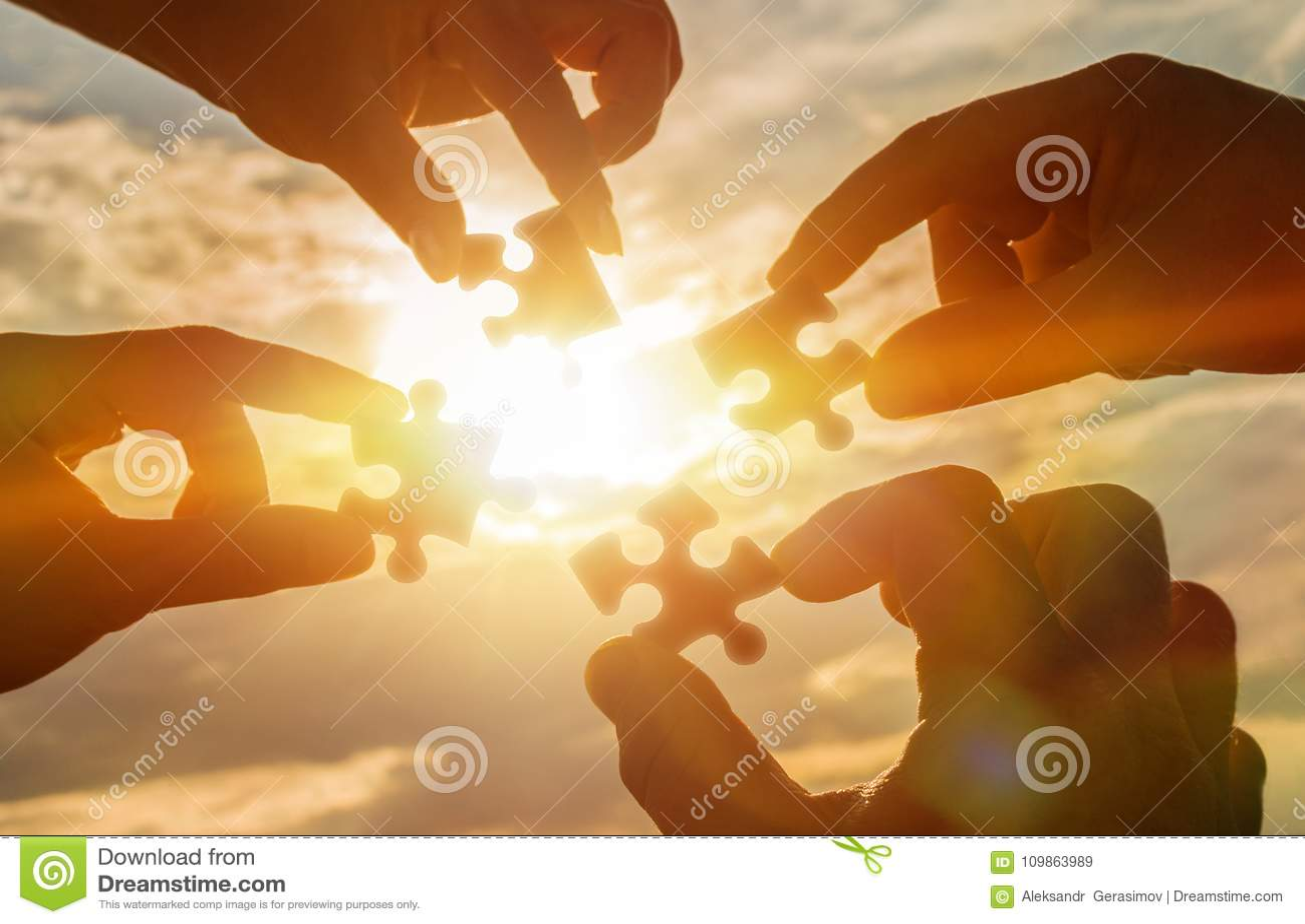 Colaboram quatro mãos que tentam conectar uma parte do enigma com um fundo do por do sol Um enigma à disposição contra a luz sola