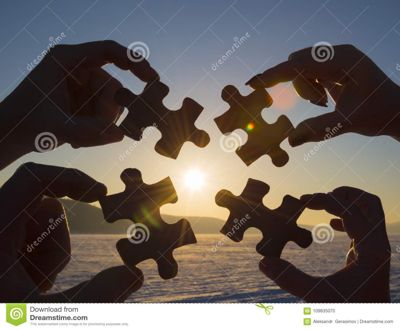 Colaboram quatro mãos que tentam conectar uma parte do enigma com um fundo do por do sol